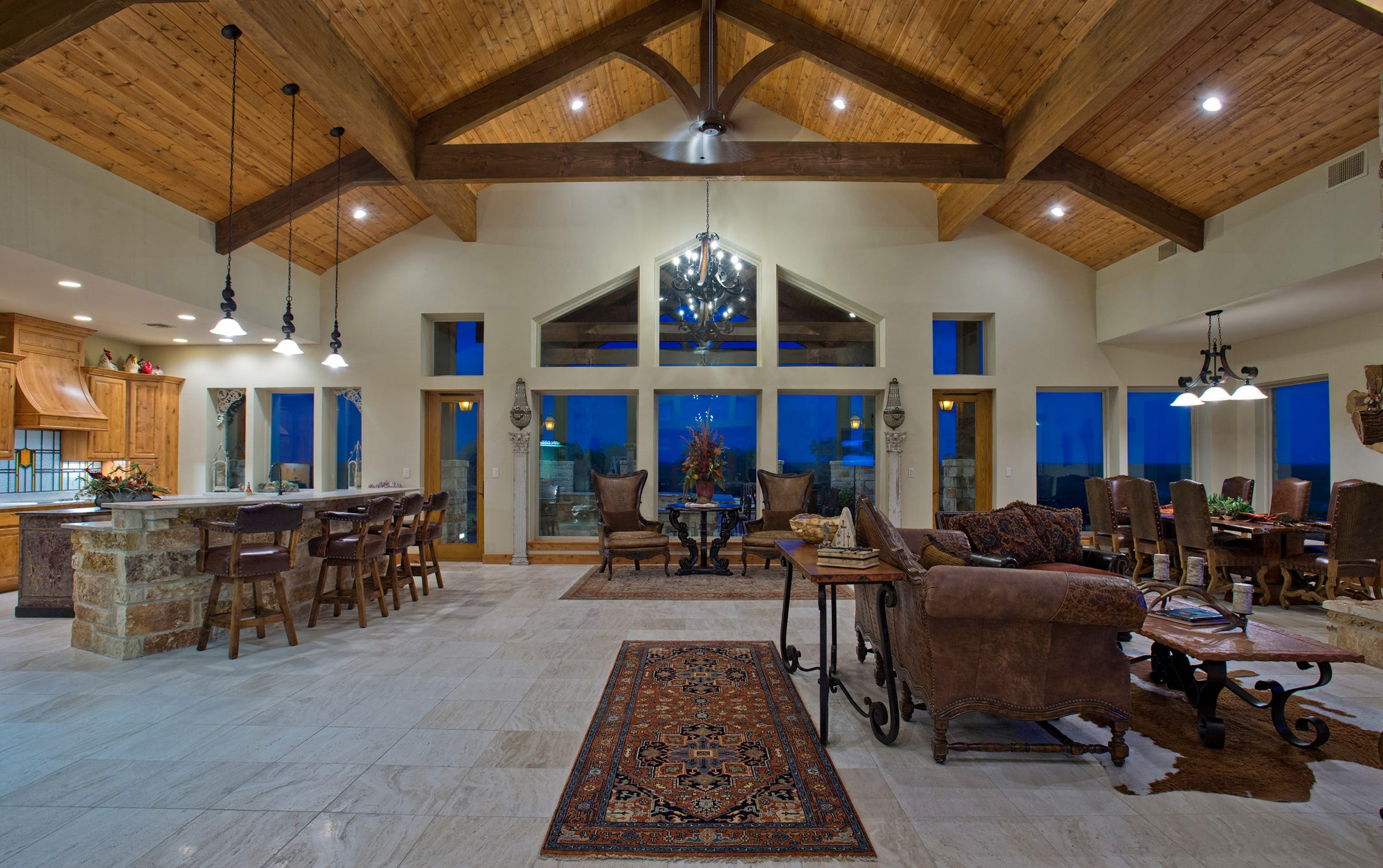 Heavy solid wood truss beams span 22ft. douglas fir wood ceilings in the massive wide open living, kitchen and dining space.  A wall of windows overlook the amazing outdoor living spaces and acreage.