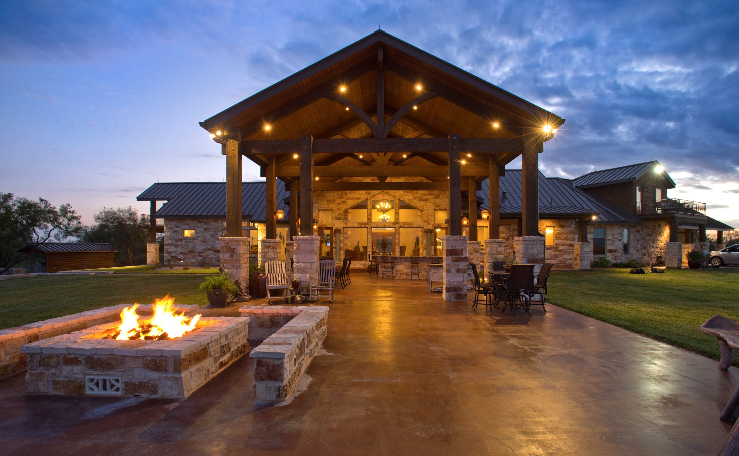 A stunning view of the massive outdoor living spaces featuring a fire pit and covered as well as open patio spaces overlooking the acreage and Nueces River