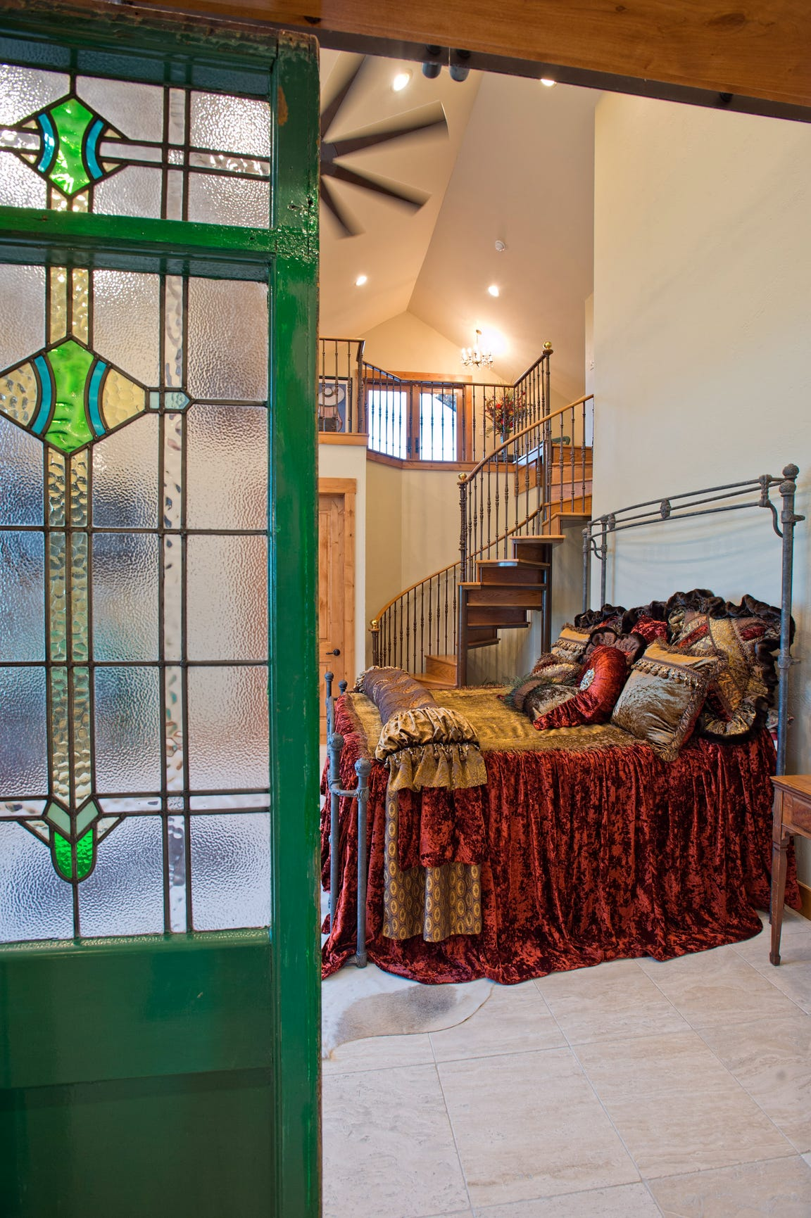 A set of antique stained glass doors lead into the master bedroom which features a unique custom designed reversing spiral staircase leading up to a loft