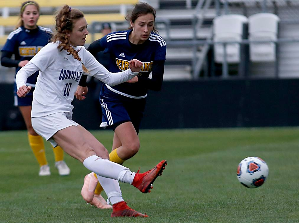 Cincinnati Country Day forward Kate Brock kicks in a goal against Kirtland midfielder Lidia Rodin during their Division III Championship soccer game at MAPFRE Stadium in Columbus Friday, Nov. 9, 2018.
