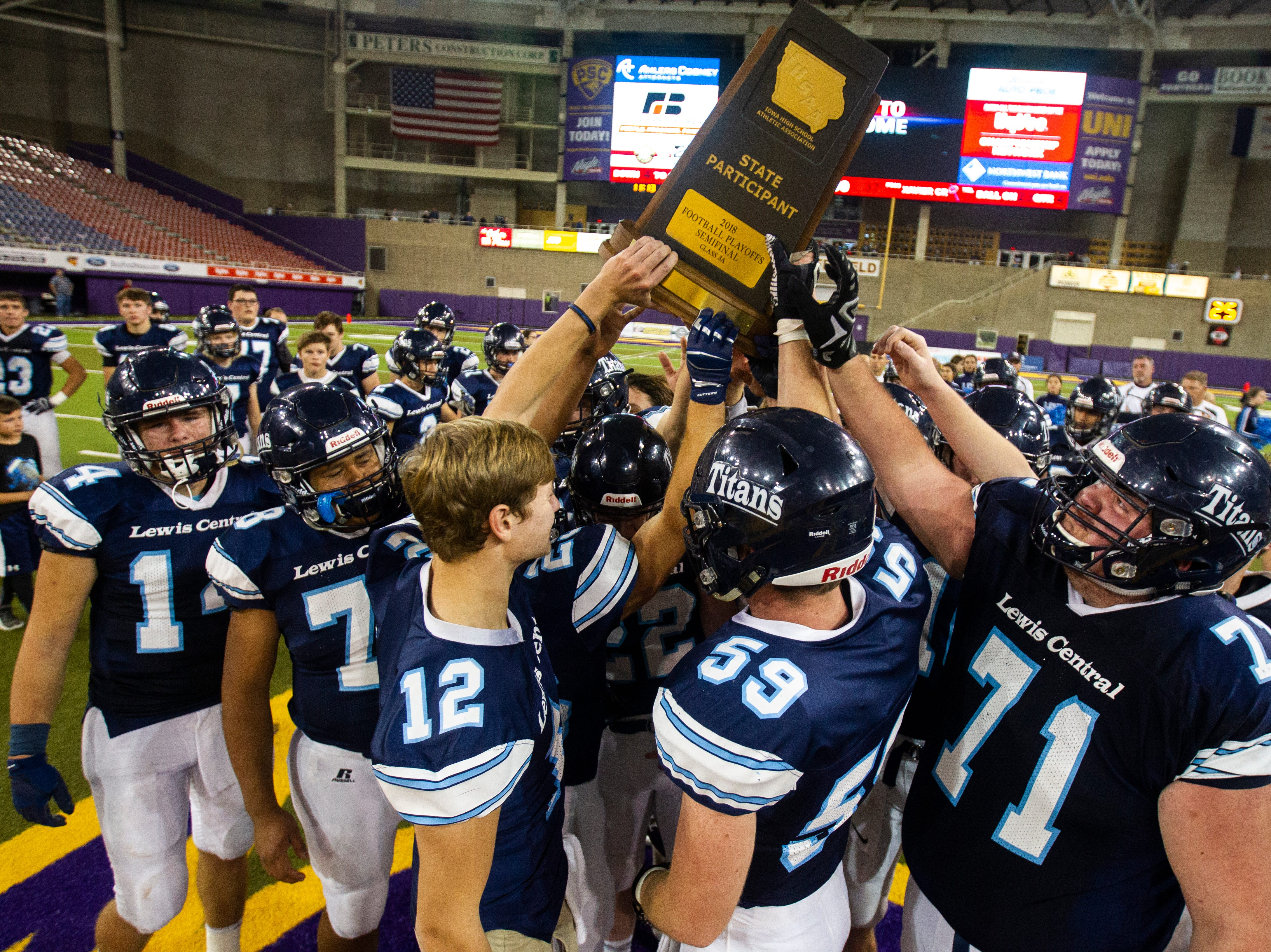 Lewis Central players hold up their state participant trophy after a Class 3A semi finals on Thursday, Nov. 8, 2018, at the UNI-Dome in Cedar Falls.