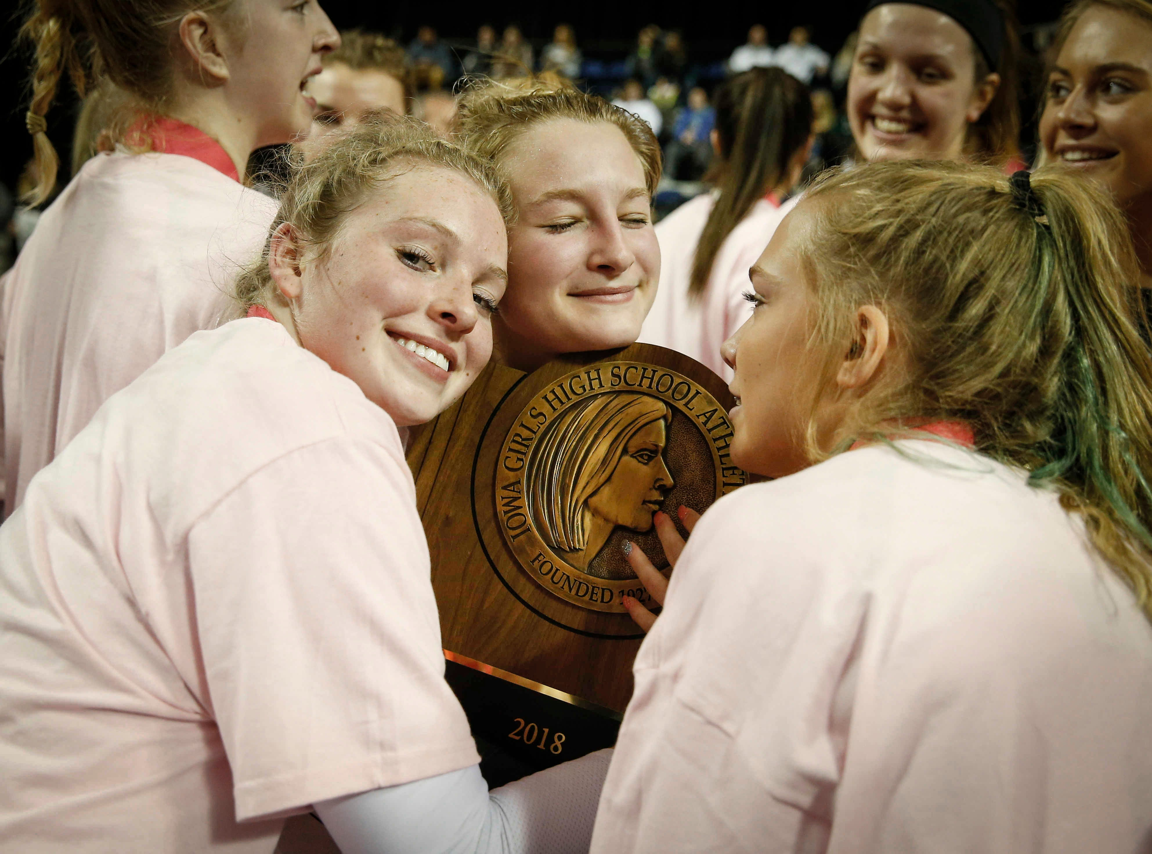 Members of the Ankeny Centennial volleyball team hug the Class 5A state championship trophy after a straight set sweep of Cedar Falls on Friday, Nov. 9, 2018, in Cedar Rapids.