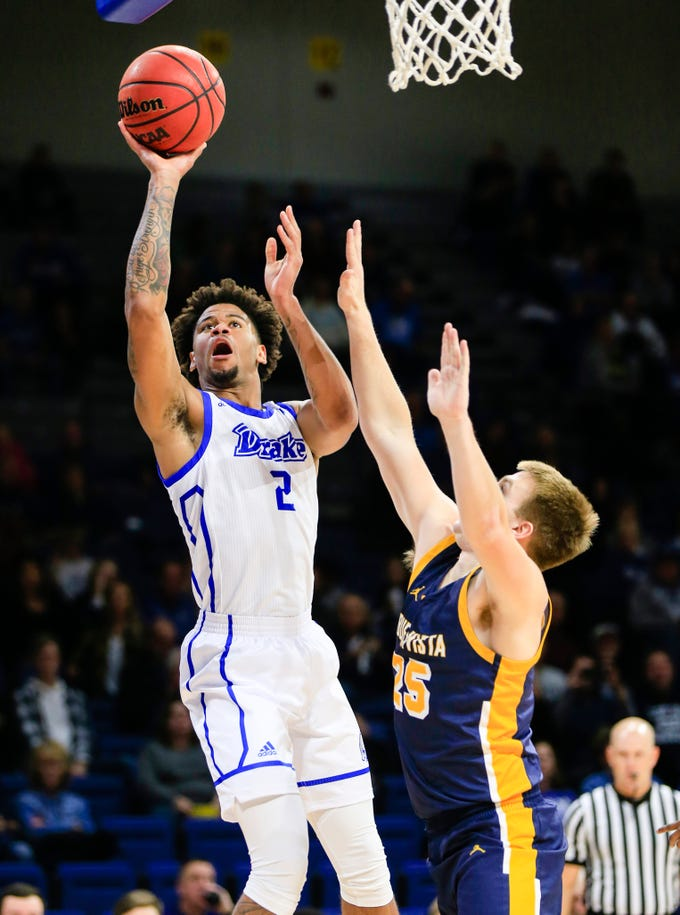 Drake's Tremell Murphy drives to the basket as Connor Sonius of Buena Vista defends during a game at the Knapp center Thursday, Nov. 8, 2018.