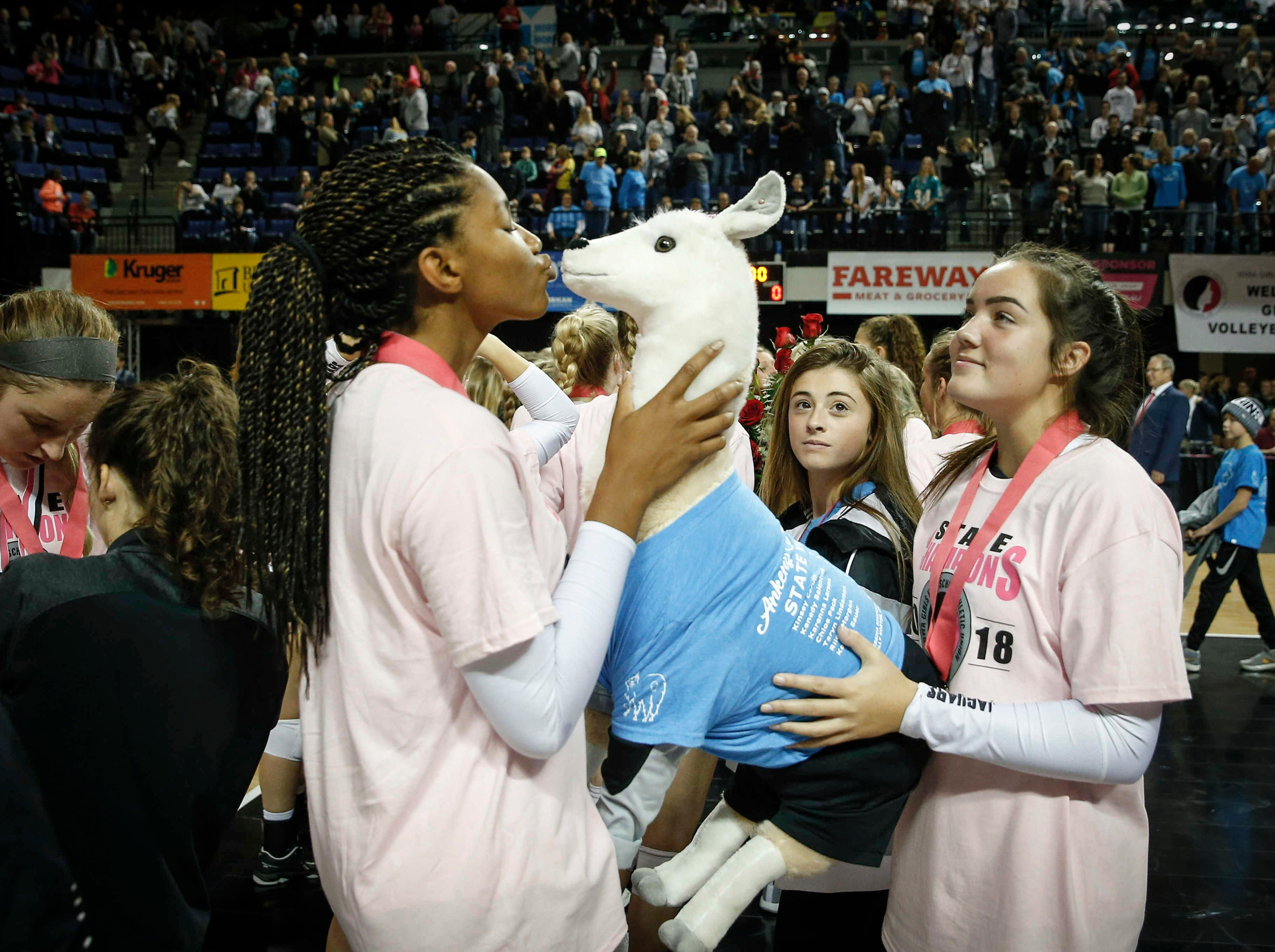 Ankeny Centennial's Devyn Robinson kisses the team's stuffed lama after the Jaguars' straight set sweep of Cedar Falls for the Class 5A state championship on Friday, Nov. 9, 2018, in Cedar Rapids.