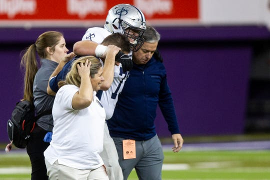 Cedar Rapids Xavier's Josh Volk (73) is helped off the field during a Class 3A semi finals on Thursday, Nov. 8, 2018, at the UNI-Dome in Cedar Falls.