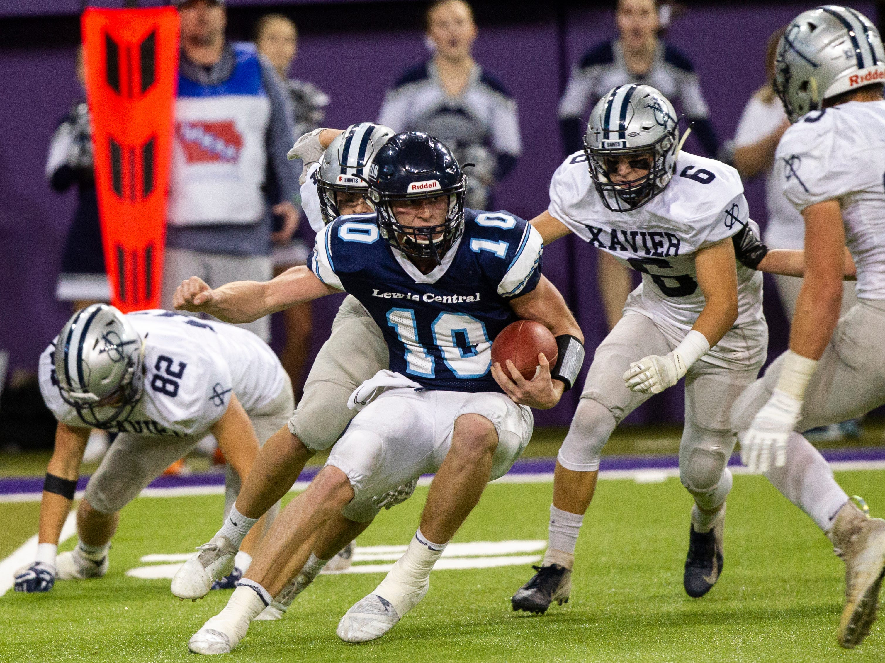 Lewis Central's Max Duggan (10) tries to evade a sack from Cedar Rapids Xavier's Bryson Bastian (6) during a Class 3A semi finals on Thursday, Nov. 8, 2018, at the UNI-Dome in Cedar Falls.