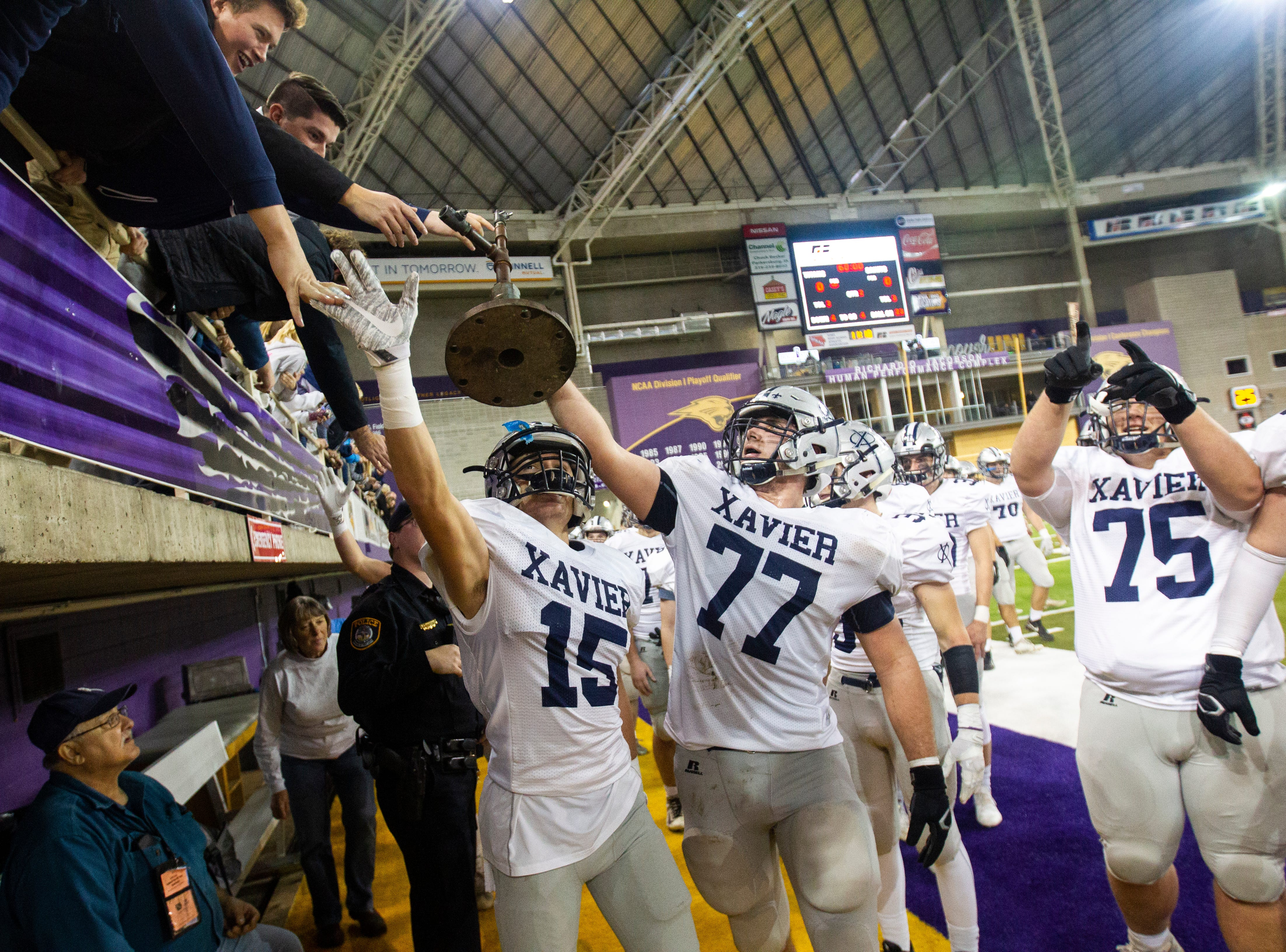 Cedar Rapids Xavier's Derrick Skala (15) and Kyle Krezek (77) celebrate with fans after a Class 3A semi finals on Thursday, Nov. 8, 2018, at the UNI-Dome in Cedar Falls.