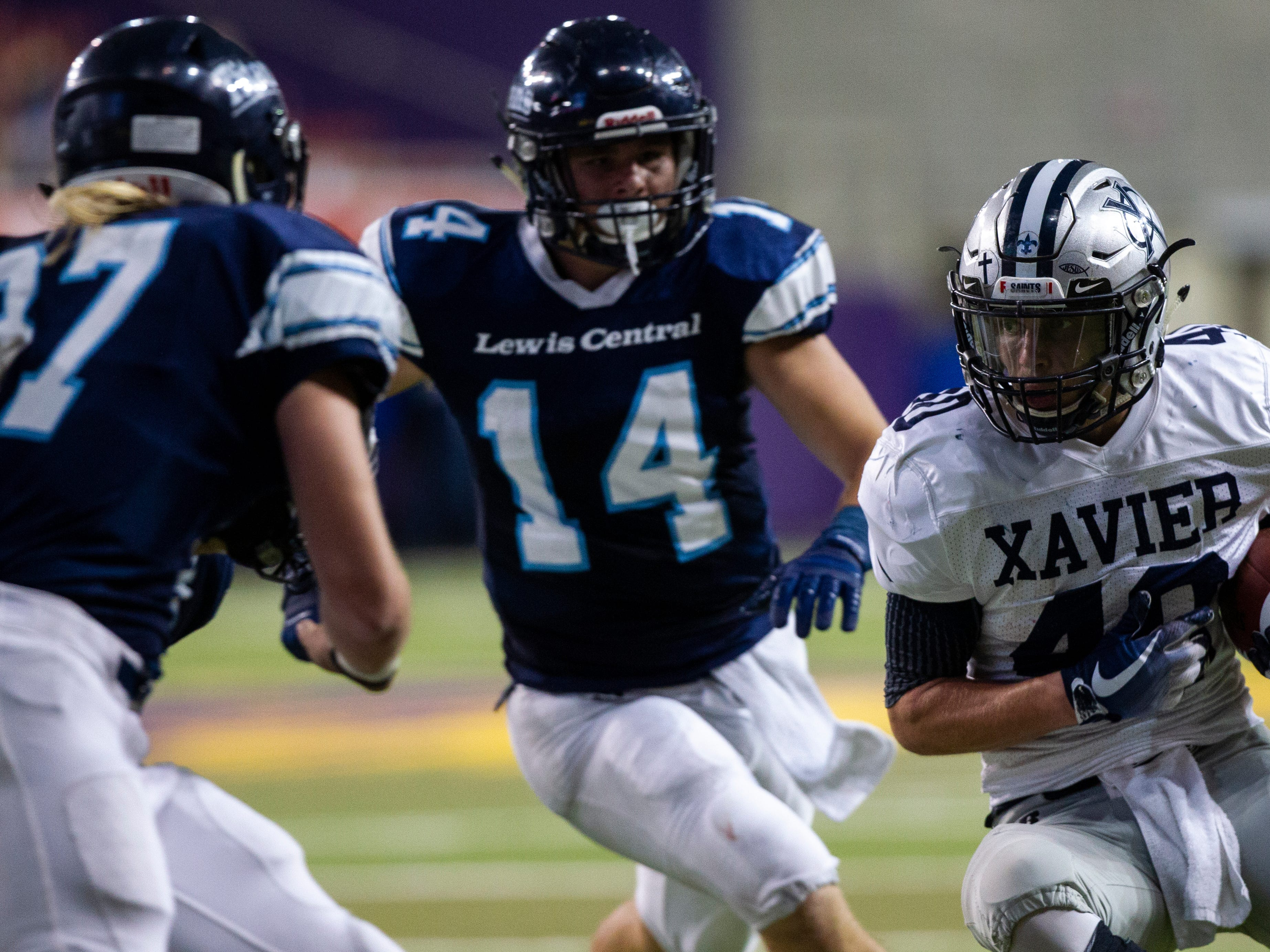 Cedar Rapids Xavier's Braden Stovie (40) gets tackled by Lewis Central's Josh Simmons (14) during a Class 3A semi finals on Thursday, Nov. 8, 2018, at the UNI-Dome in Cedar Falls.