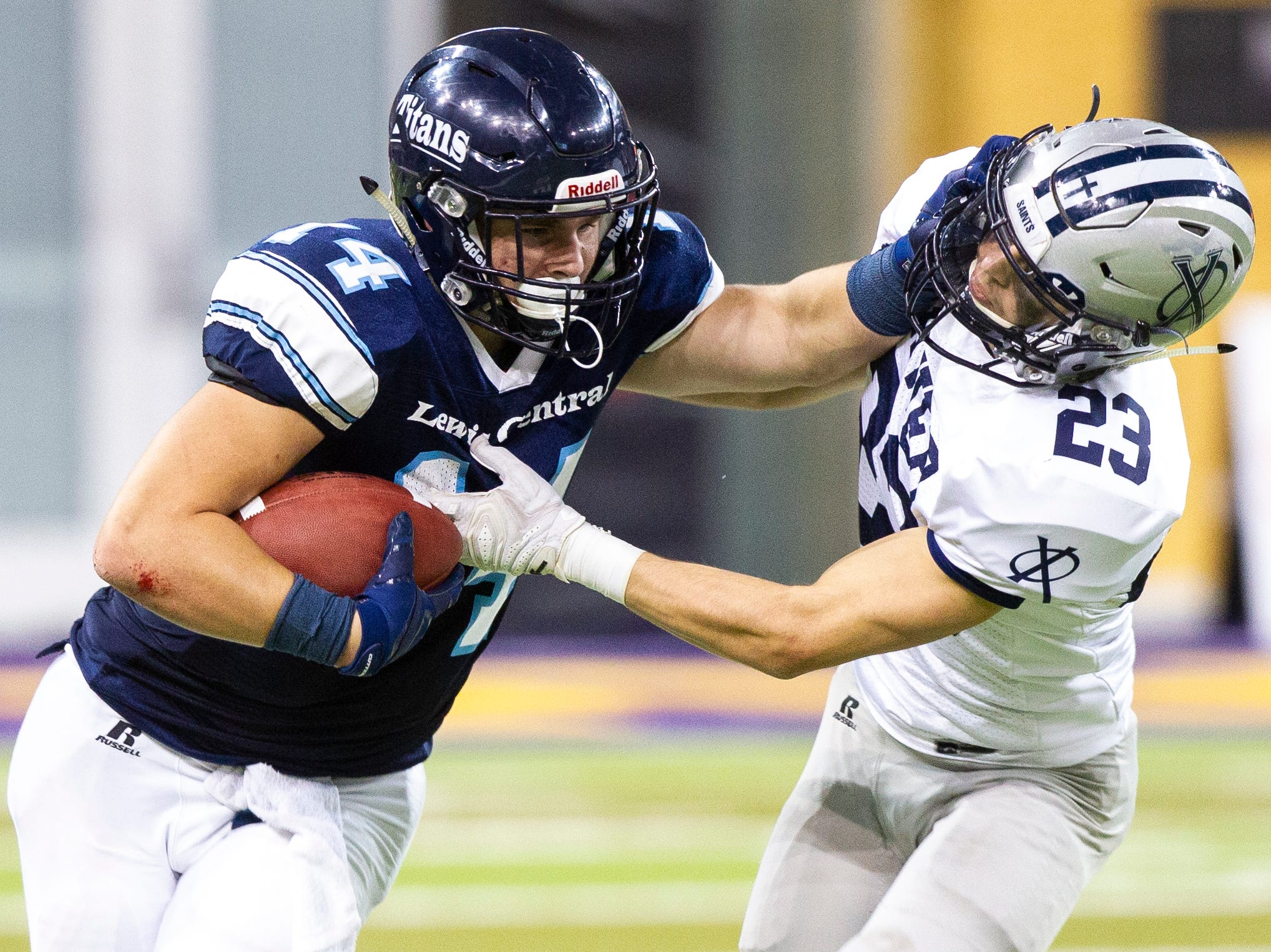 Lewis Central's Josh Simmons (14) stiff arms Cedar Rapids Xavier's Michael Gundacker (23) during a Class 3A semi finals on Thursday, Nov. 8, 2018, at the UNI-Dome in Cedar Falls.