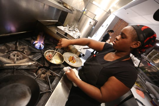Ariell Boyd, a line cook at Marrow in Detroit's West Village neighborhood, prepares a dish. The entire kitchen staff at the new restaurant are salaried employees who receive paid time off and health benefits.