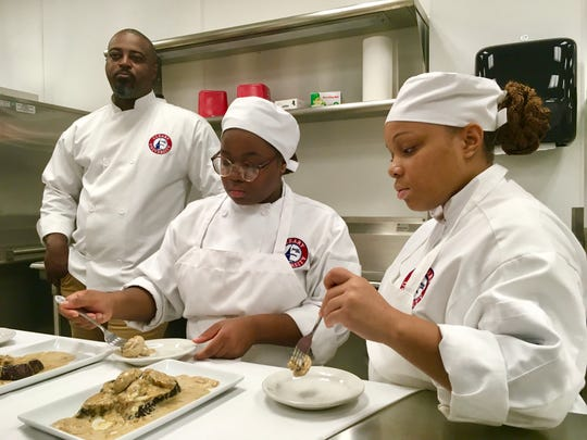 Cleary University Chef-in-Residence Max Hardy with culinary students Keirra Williams, left, and Brittany Williams as they sample dishes prepared together.