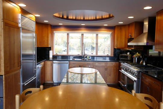 Natural cherry cabinets run through the kitchen among many rooms. A dome cut into the ceiling is painted blue and lighted. The island combines round cabinets with rectangular glass.