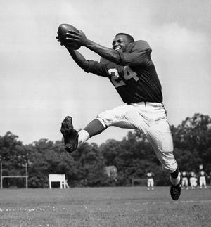 In this July 30, 1953 photo, halfback Wally Triplett poses in action during his second year with the Chicago Cardinals and fourth year in the National Football League.