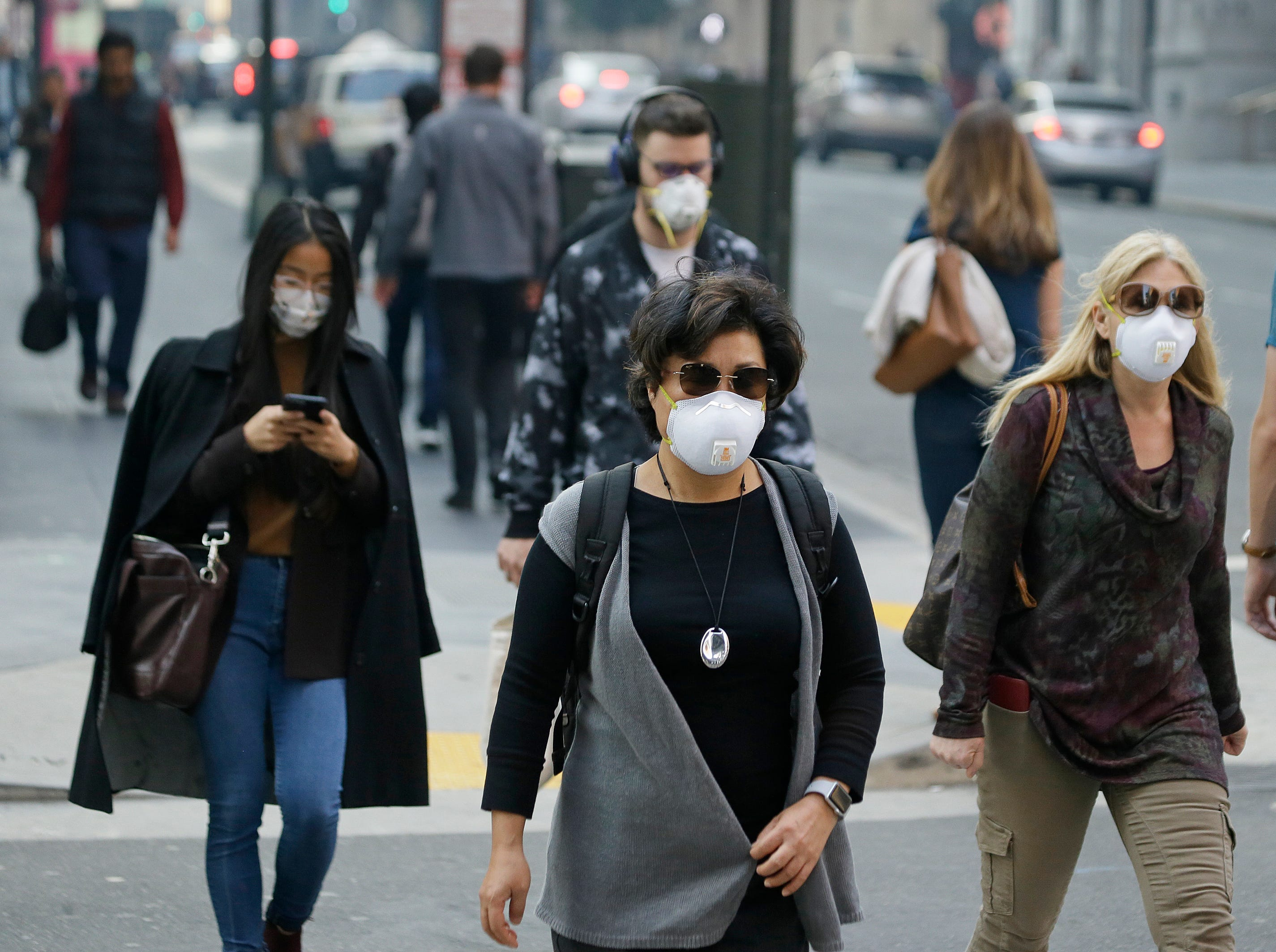 People wear masks while walking through the Financial District in the smoke-filled air Friday, Nov. 9, 2018, in San Francisco. Authorities have issued an unhealthy air quality alert for parts of the San Francisco Bay Area as smoke from a massive wildfire drifts south, polluting the air. Officials say the thousands of structures in the town of Paradise, 180 miles northeast of San Francisco, were destroyed by the blaze that has charred 110 square miles.