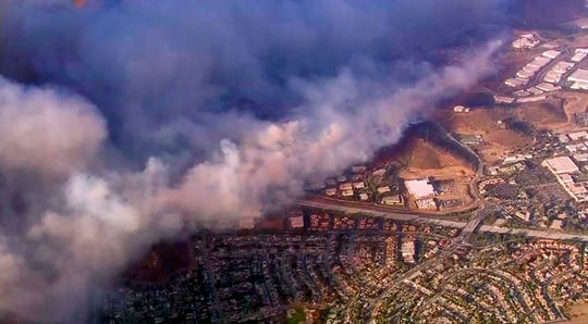 This photo taken from video provided by CBS2/KCAL9 shows a wildfire burning in Camarillo, Calif., Thursday afternoon, Nov. 8, 2018. Known as the Hill fire, it here has crossed U.S. Highway 101, at center right, potentially threatening hundreds of homes.