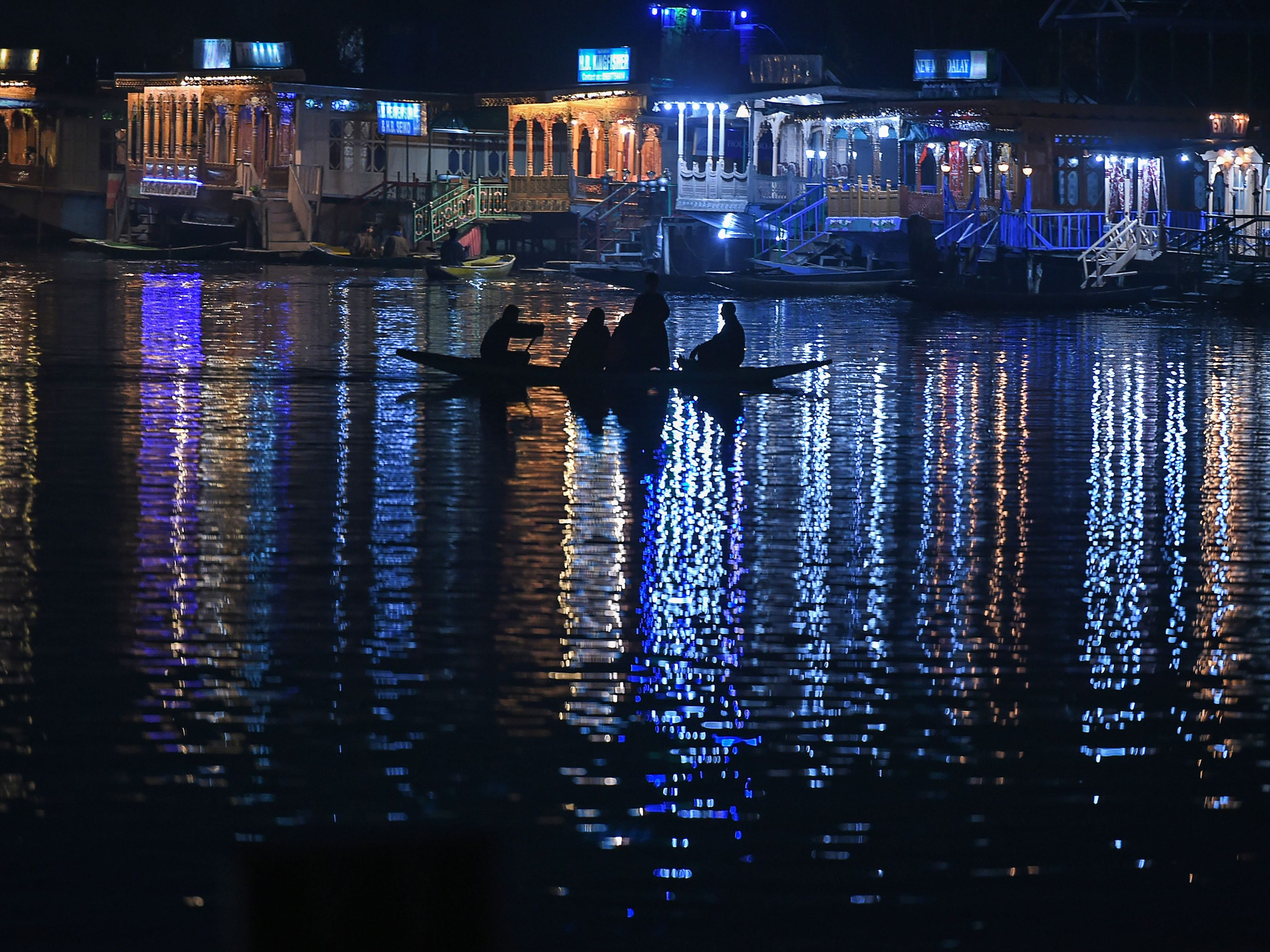 A Kashmiri boat operator transports residents across Dal Lake next to house boats in Srinagar on November 9, 2018.