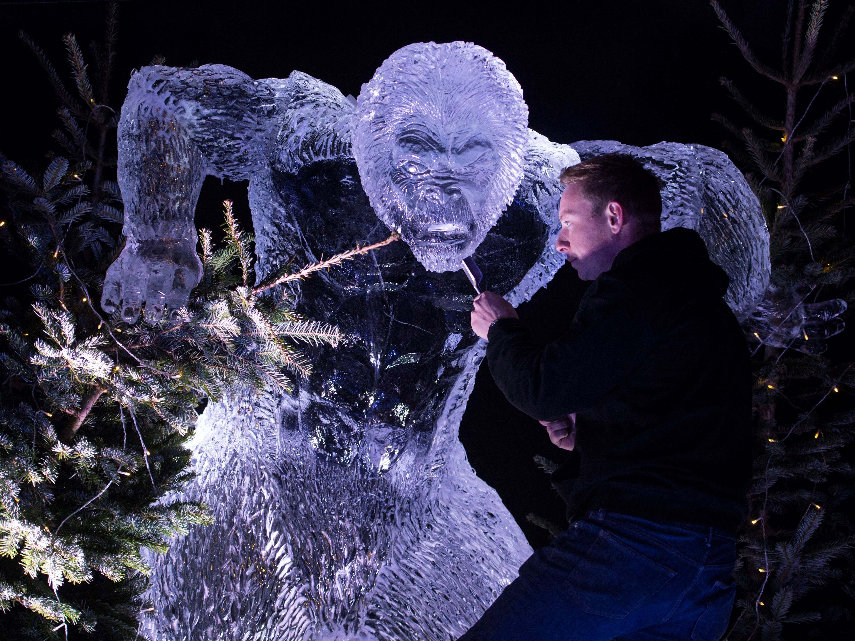 Ice sculptor Mark Hackney puts the finishing touches to a yeti carved from ice in the 'Ice Village', during a photocall to promote the 'Ice Village', in central Manchester, northern England on November 9, 2018. - The Ice Village Manchester, which is open until January 5, 2019, features an ice cavern, ice sculptures and frozen ice bar all carved using 250 tonnes of solid ice.