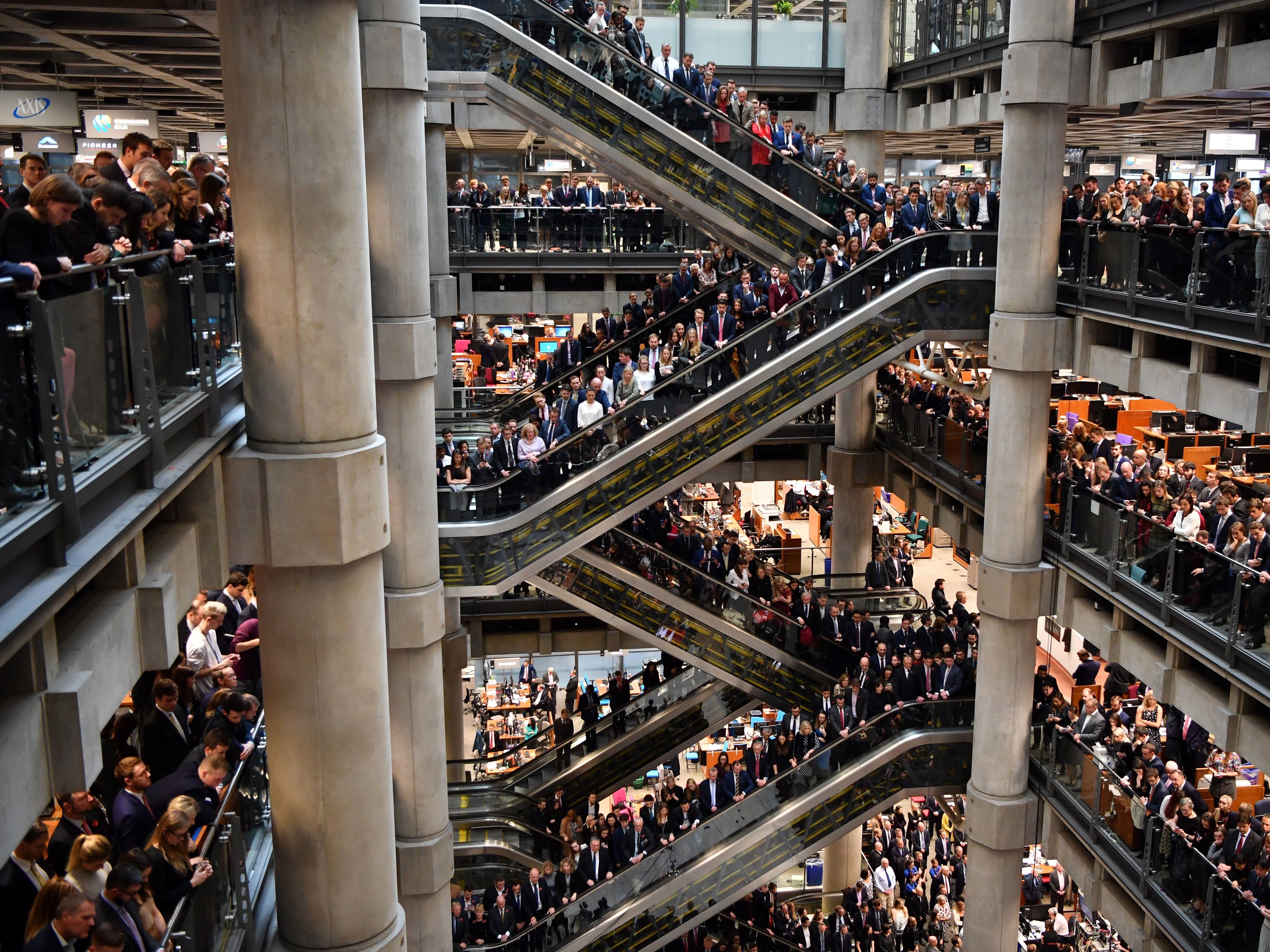 Employees observe a minute's silence in commemoration of Remembrance Day inside Lloyd's of London in the city of London on November 9, 2018. - November 11, 2018 will be the 100th anniversary of the end of WWI. In the run-up to Armistice Day, many Britons wear a paper red poppy -- symbolising the poppies which grew on French and Belgian battlefields during World War I.