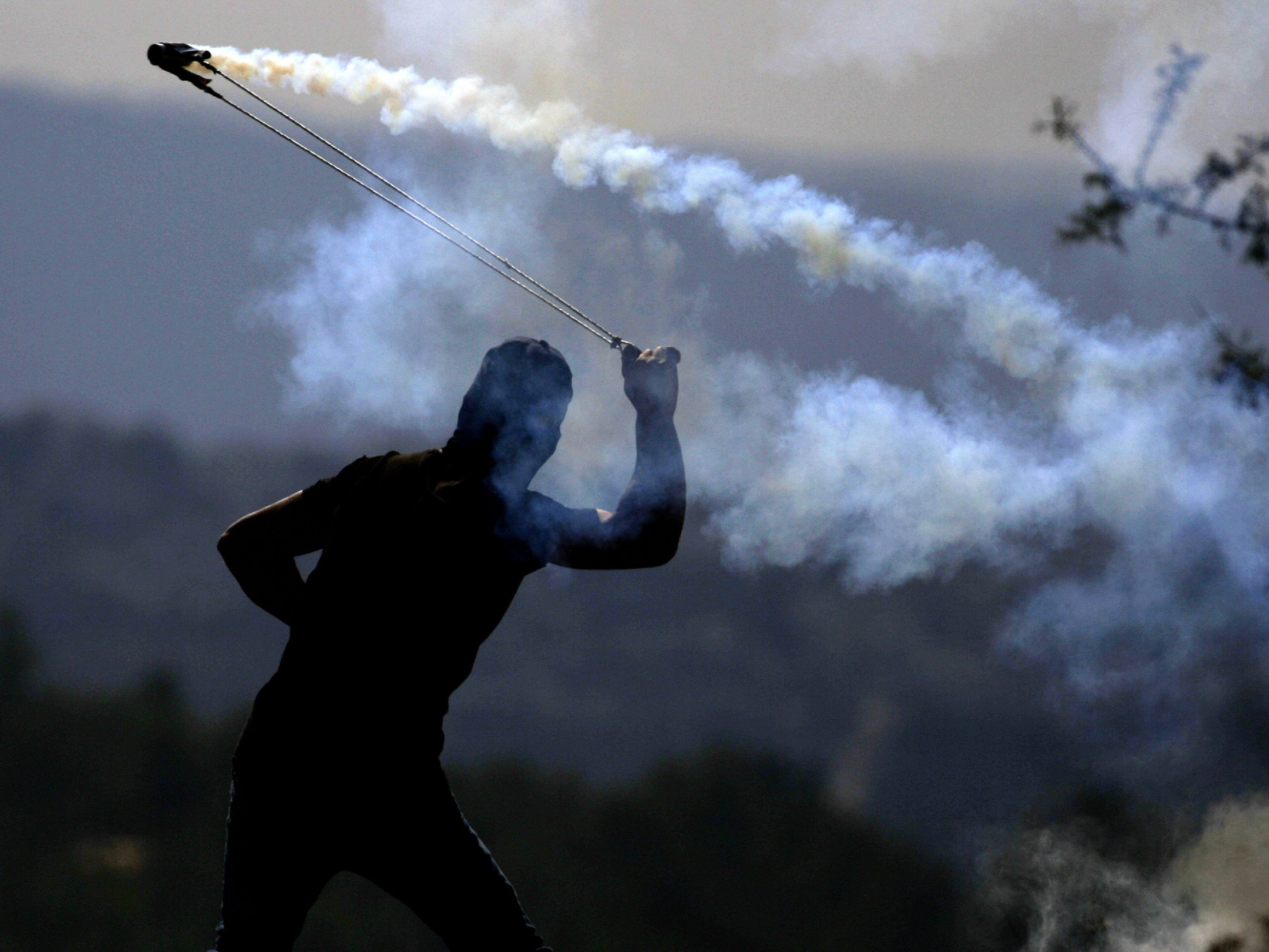 A Palestinian protester throws a tear gas canister towards Israeli soldiers who fired it during a demonstration against Israeli land seizures for Jewish settlements, in the village of Ras Karkar, near Ramallah in the occupied West Bank on November 9, 2018.