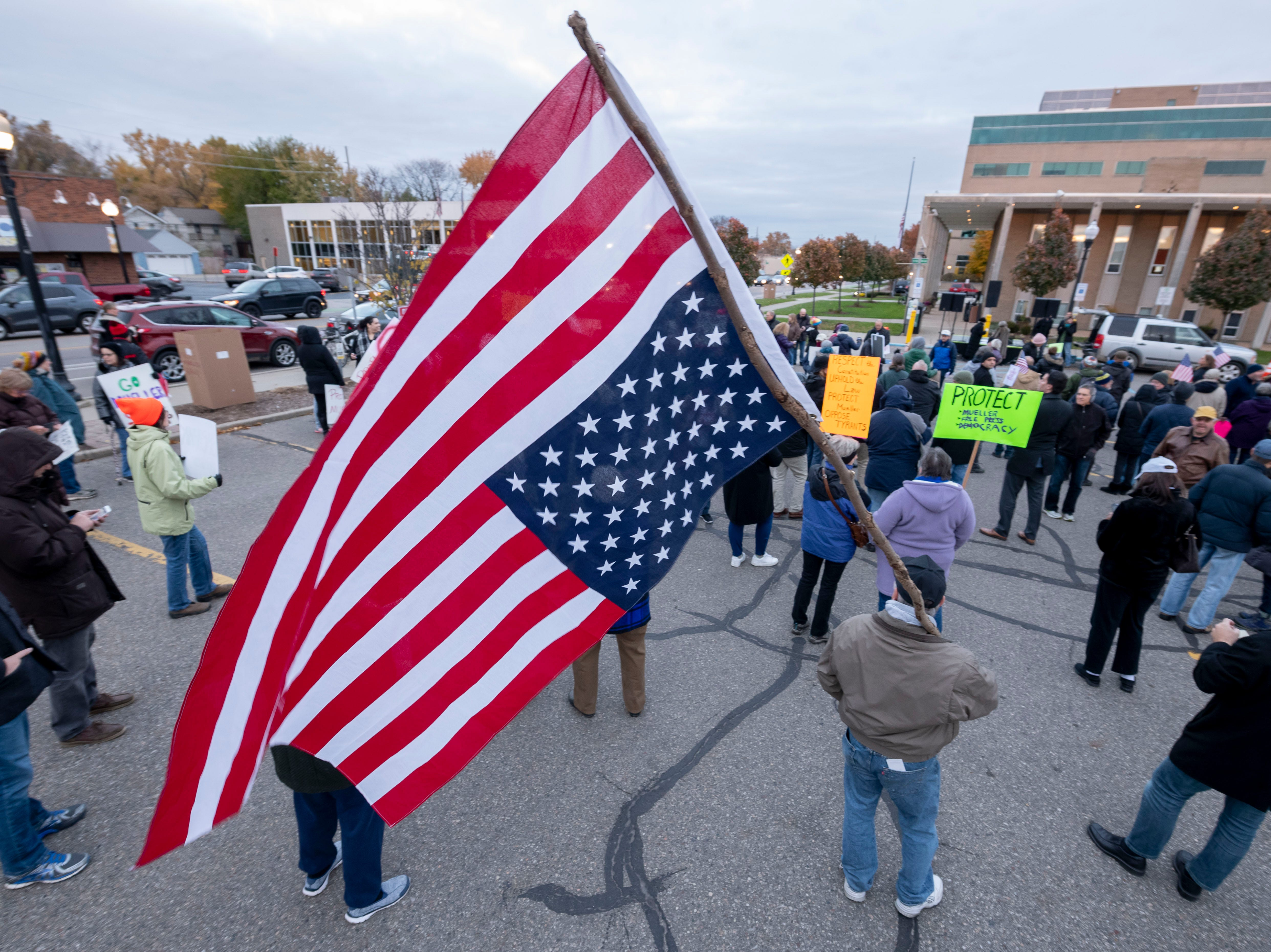 A protester holds an upside down American flag, a sign of extreme distress, during a protest at Ferndale City Hall.