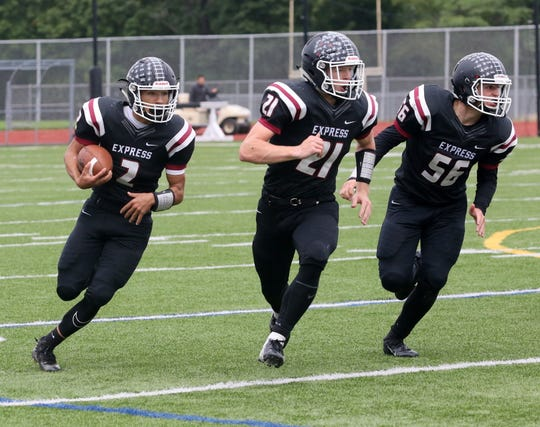 Ethan Simpson of Elmira carries the ball as fullback Nate Latshaw (21) and offensive lineman Zach Miller (56) block during a 30-8 win over Corcoran on Sept. 22, 2018 at Ernie Davis Academy.