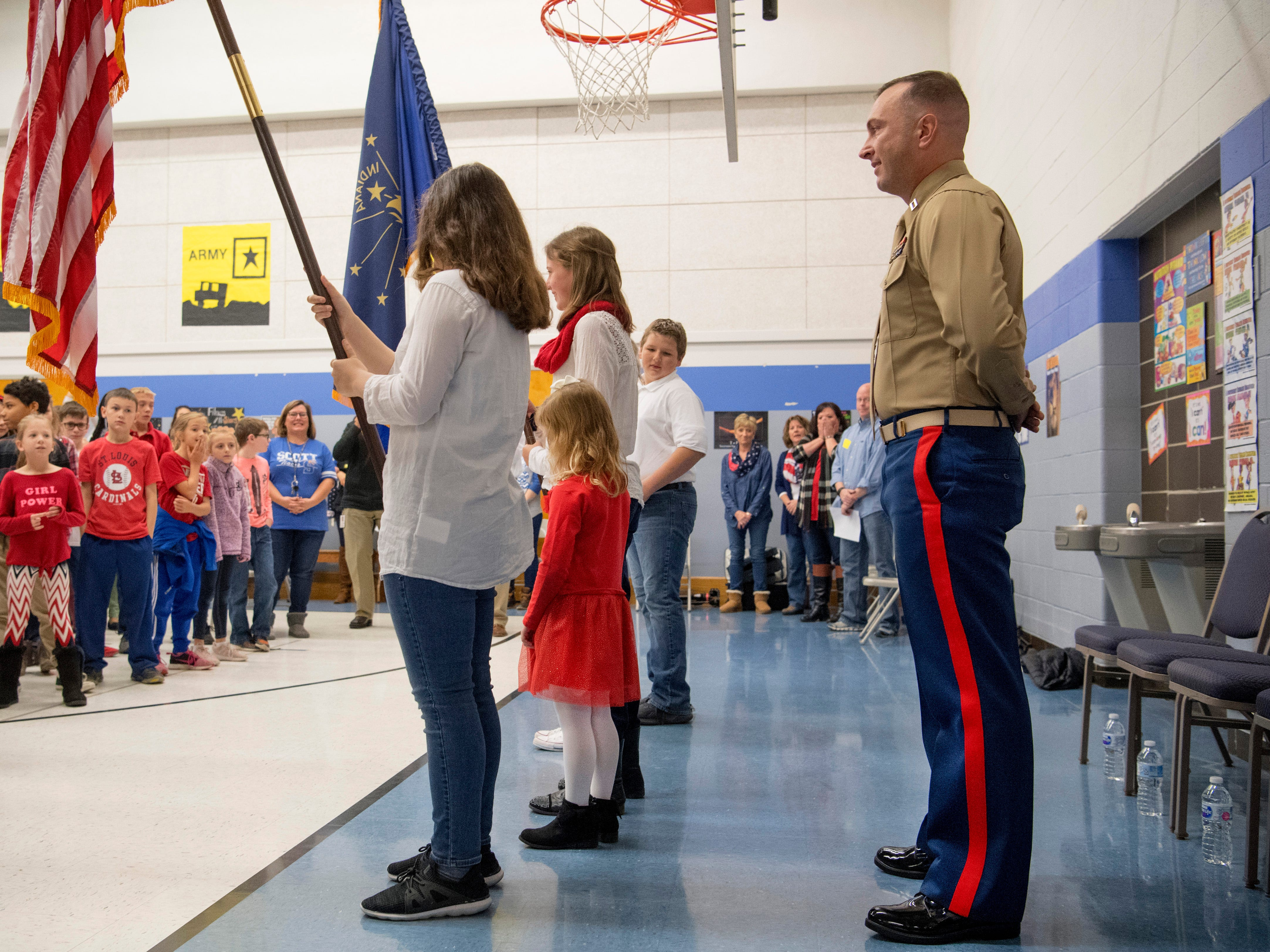 Scott Elementary School kindergartner Eliana Marzec, 5, center, is unaware of her father, Marine Corps Capt. Ryan Marzec, standing at parade rest during the Veterans Day program Friday morning. Captain Marzec returned from a tour in Afghanistan and surprised the eldest of his three daughters.