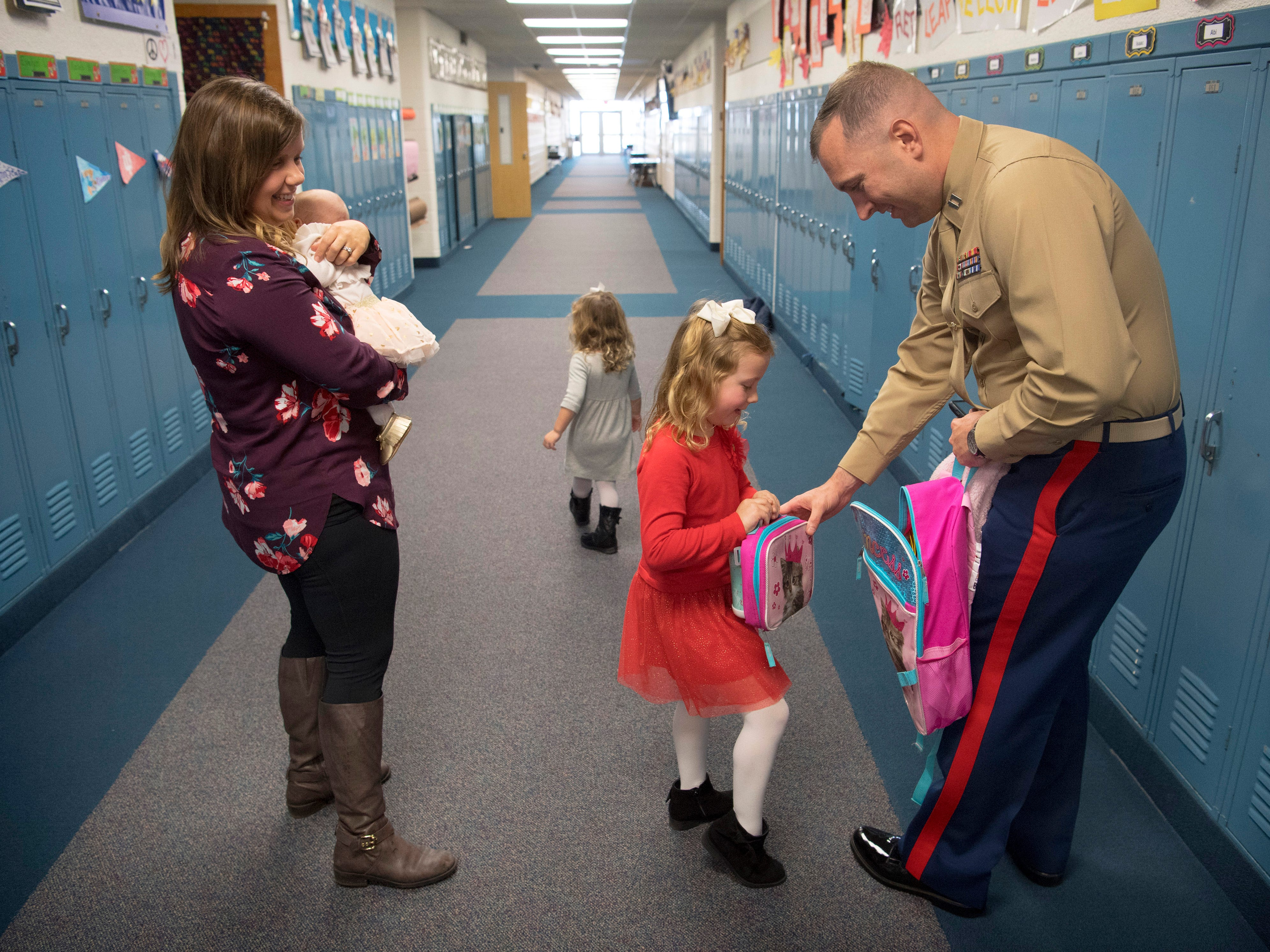 "Eliana Marzec, 5, packs up her ""lunch"" with help from her dad, Capt. Ryan Marzec, before heading home for the weekend with her mom, Katie, and sisters Kyra, 2, and Hailey, 7 weeks, Friday morning. Knowing Elaina was going to go home early (even thought Elaina had no idea), mom confessed to packing just water in her thermos and putting an ice pack inside her lunch box. Eliana hadn't seen her father since he deployed to Afghanistan with the Marine Corps Reserve January 1, 2018."
