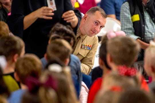 Capt. Ryan Marzec peeks around the musical director to get a look at his daughter, kindergartner Eliana, 5, at the Scott Elementary School Veterans Day program Friday morning.