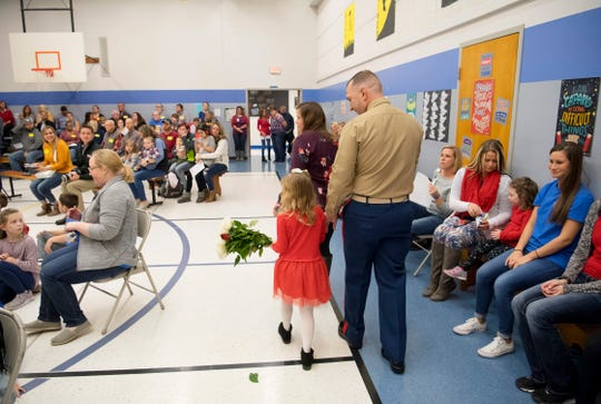Scott Elementary School kindergartner Eliana Marzec, 5, center, heads to her reserved seats with her father, Marine Corps Capt. Ryan Marzec, during the Veterans Day program Friday morning. Captain Marzec returned from a tour in Afghanistan and surprised the eldest of his three daughters with the visit.