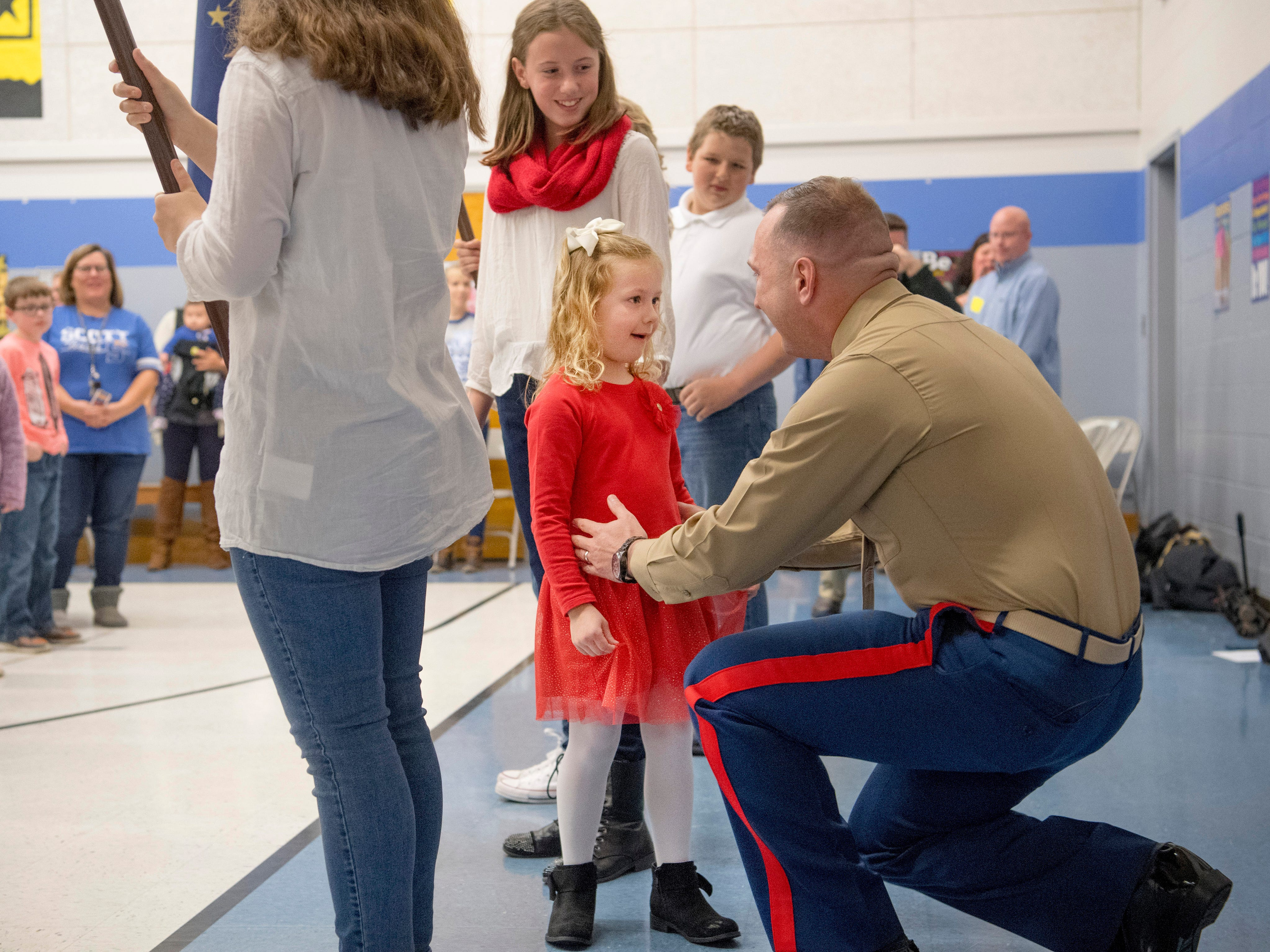 Scott Elementary School kindergartner Eliana Marzec, 5, center, is surprised to find her father, Marine Corps Capt. Ryan Marzec, standing behind her during the Veterans Day program Friday morning. Captain Marzec returned from a tour in Afghanistan and surprised the eldest of his three daughters.