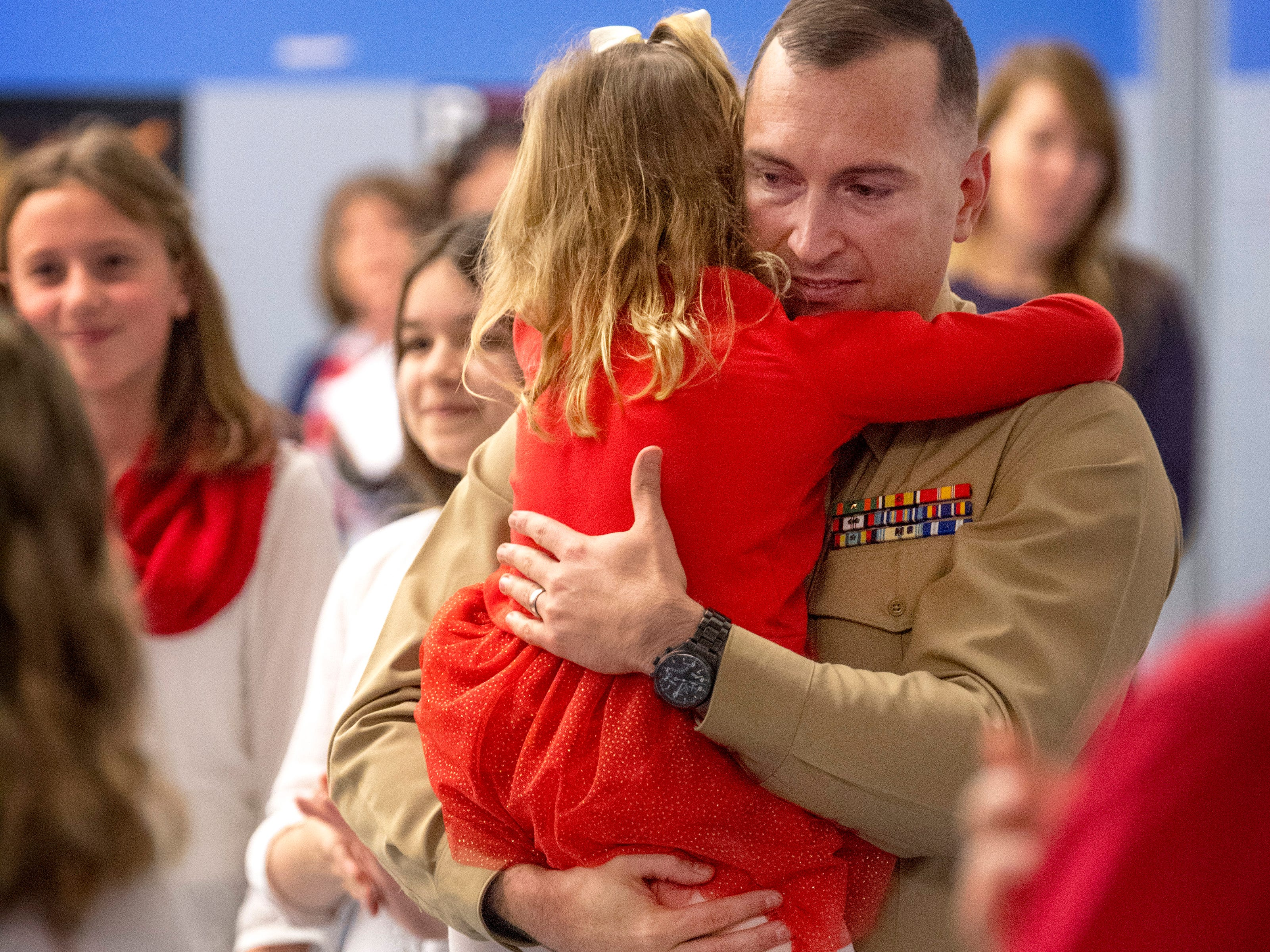 Scott Elementary School kindergartner Eliana Marzec, 5, center, clutches her father, Marine Corps Capt. Ryan Marzec, moments after he surprised her with a visit during the Veterans Day program Friday morning. Captain Marzec returned from a tour in Afghanistan in time to pull off the surprise of the eldest of his three daughters.