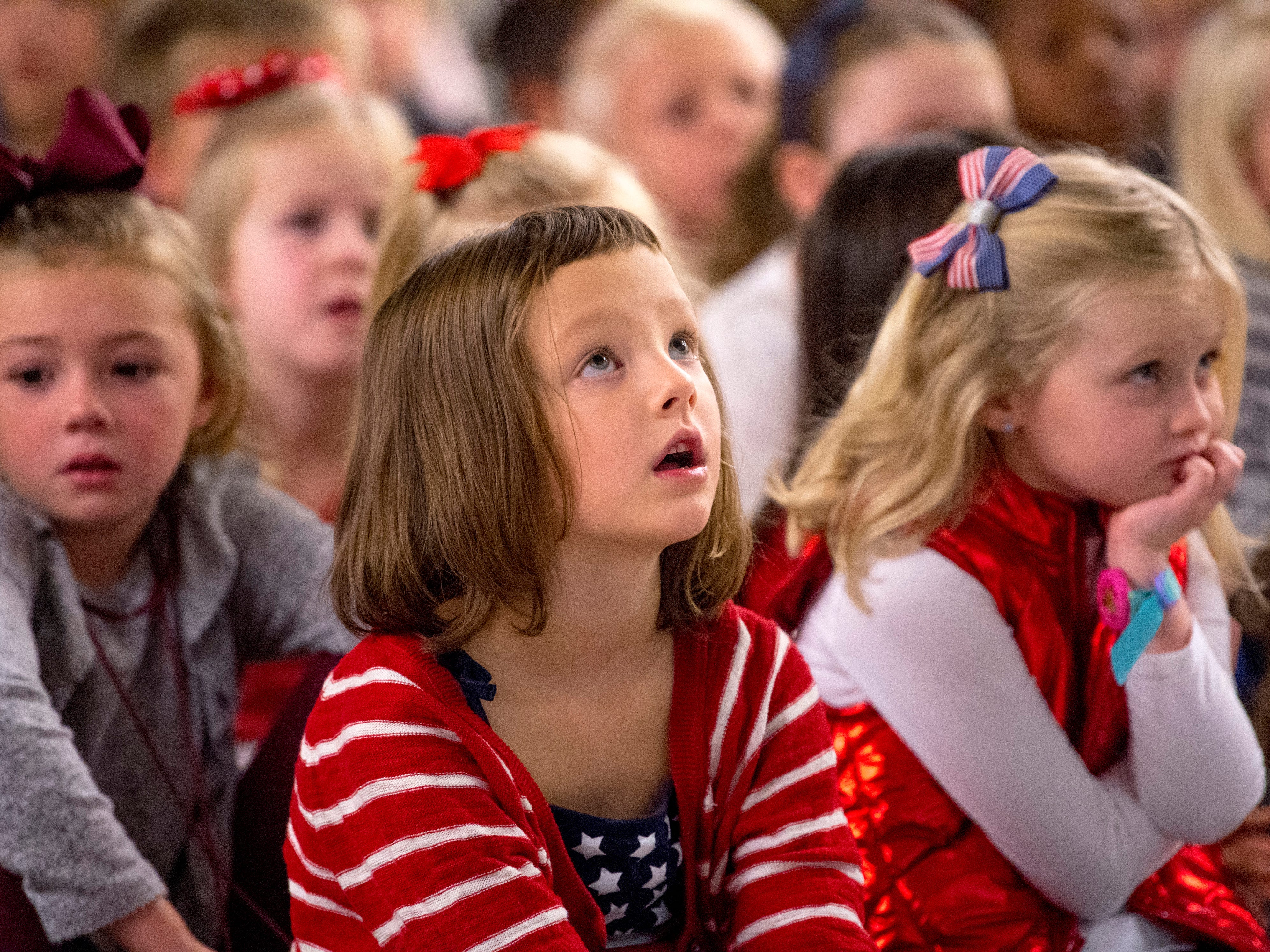 """Heidi Veirs, 6, a kindergartner at Scott Elementary School, watches the slideshow accompaniment to the """"Armed Forces Medley"""" during the school's Veterans Day program Friday morning."""