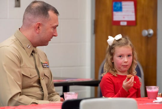 """Capt. Ryan Marzec has refreshments with his daughter, Eliana, 5, after the Scott Elementary School Veterans Day program Friday morning. """"She hasn't warmed up to him yet,"""" her mom, Katie Marzec said. """"But she'll come around."""" Eliana hadn't seen her father since he deployed to Afghanistan with the Marine Corps Reserve January 1, 2018."""