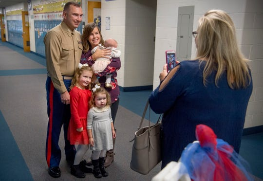 Laura Stilwell, a volunteer parent at Scott Elementary School, asks the Marzec Family, including, Capt. Ryan Marzec, Katie Marzec, Eliana, 5, Kyra, 2, and Hailey, 7 weeks, to posed for a picture after school's Veterans Day program Friday morning.