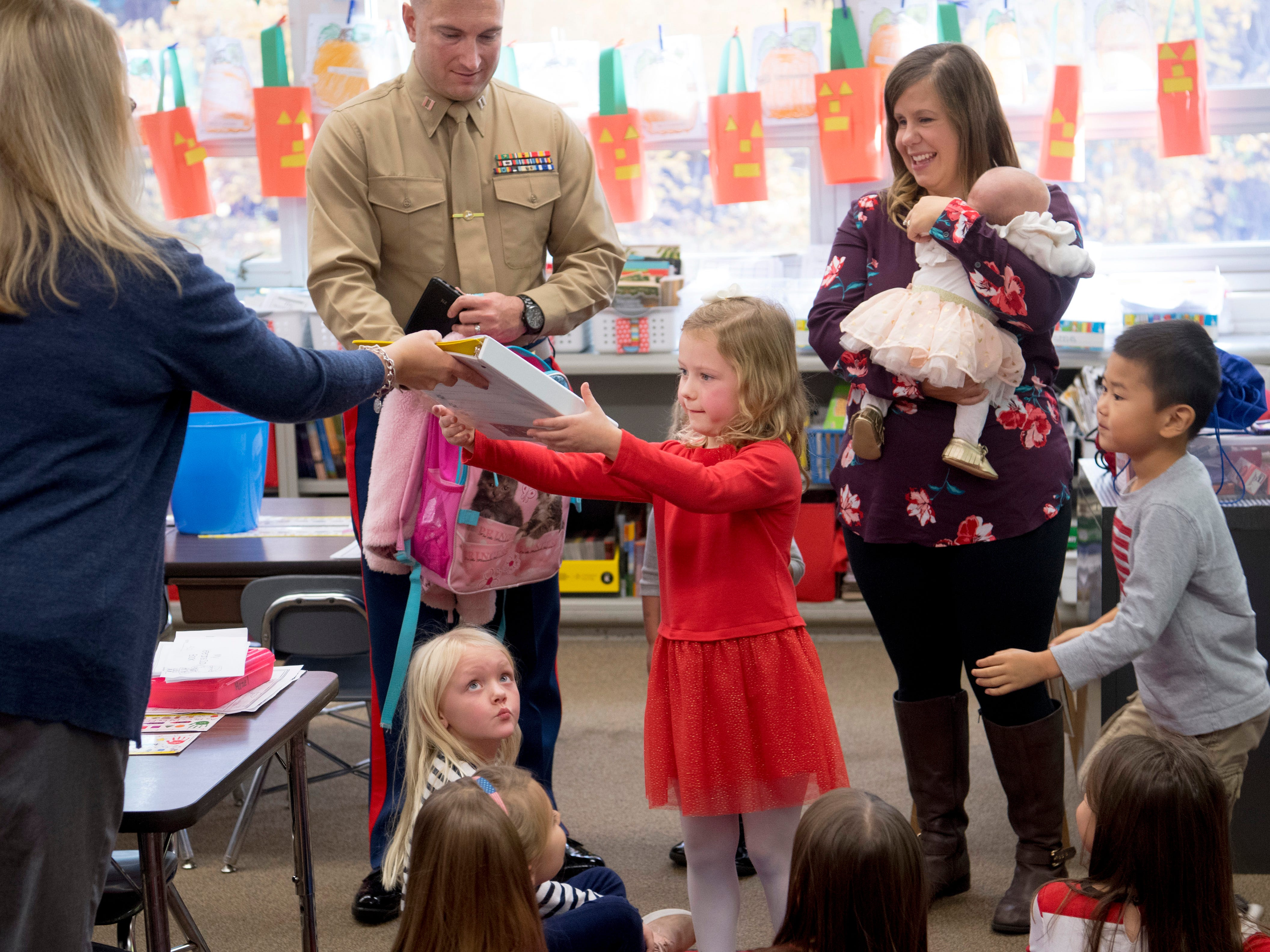 Eliana Marzec, 5, receives her homework from her kindergarten teacher before heading home for the weekend Friday morning. Eliana hadn't seen her father, Capt. Ryan Marzec, upper left, since he deployed to Afghanistan with the Marine Corps Reserve January 1, 2018. Also pictured are mom, Katie, and 7-week-old sister Hailey.
