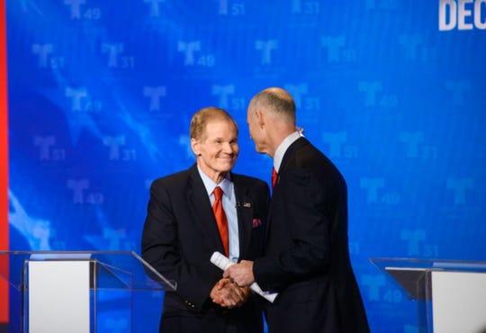 U.S. Sen. Bill Nelson and Florida Gov. Rick Scott shake hands at a Senate debate in Miramar, Florida, on Oct. 23, 2018.
