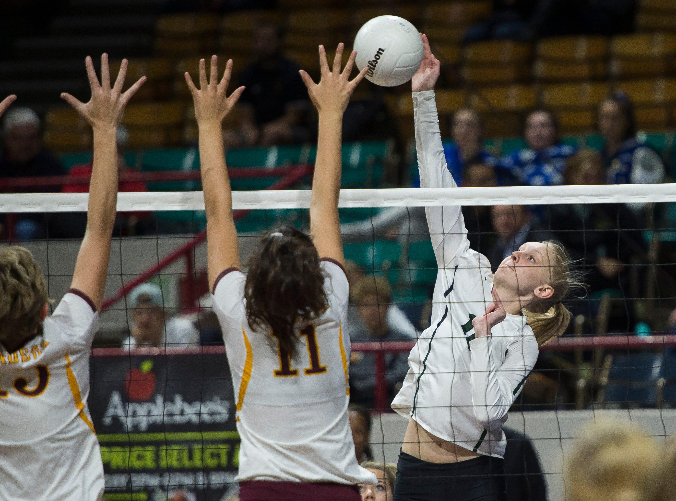 Fossil Ridge High School senior Catie Semadeni (16) spikes the ball past Windsor High School junior Adison Moyer (15) and junior Ellie Garrett (11) on Thursday, Nov. 8, 2018, at the Denver Coliseum in Denver, Colo.