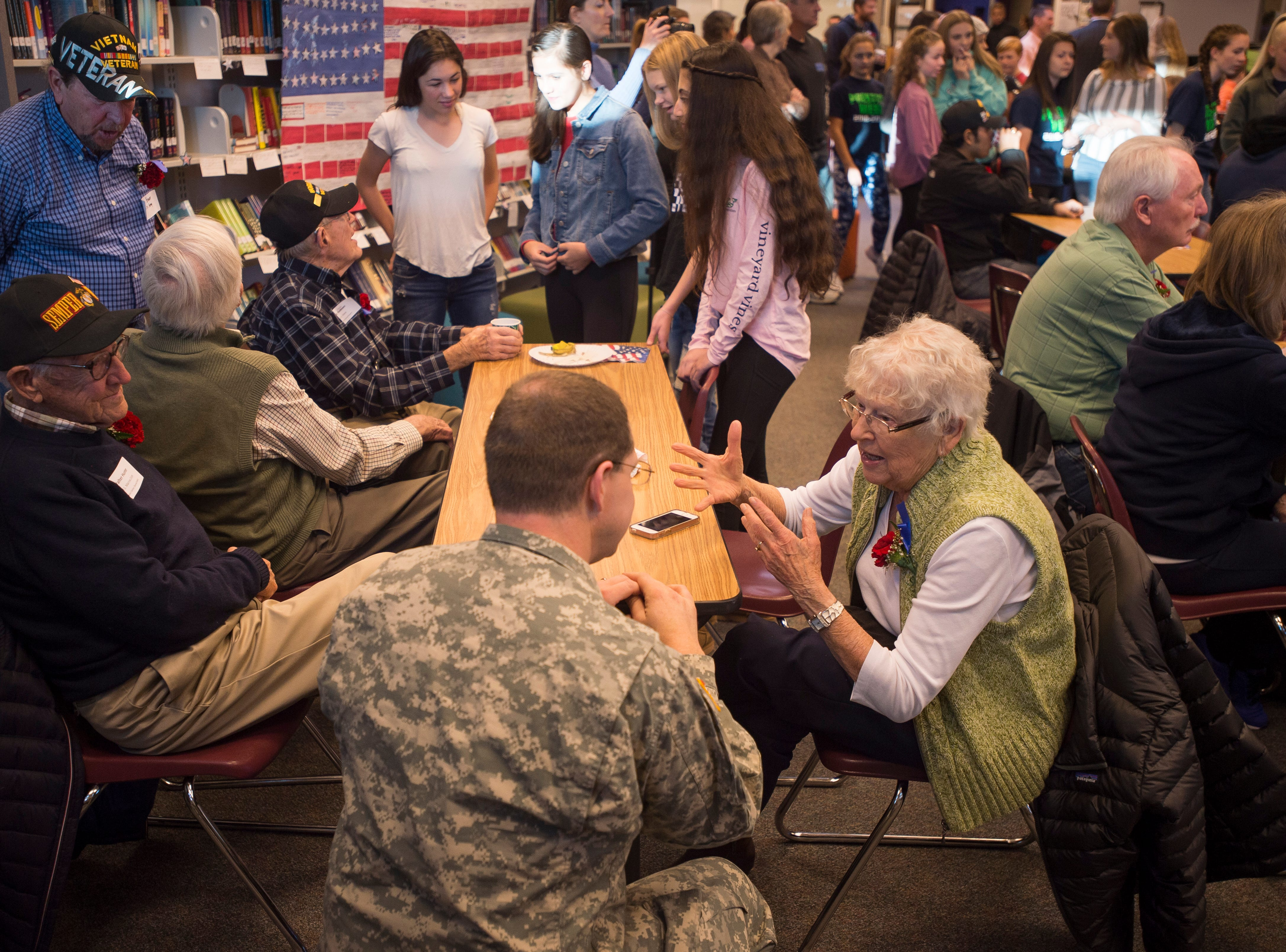 World War II Cadet Nurse Corps veteran Irene Hunter, right, and her husband of nearly 72 years, United States Marine Corps veteran Walter Hunter, left, talk with Army Reserve veteran Tom Scott during Preston Middle School's fourth annual Veterans Day Breakfast on Friday, Nov. 9, 2018, at Preston Middle School in Fort Collins, Colo.