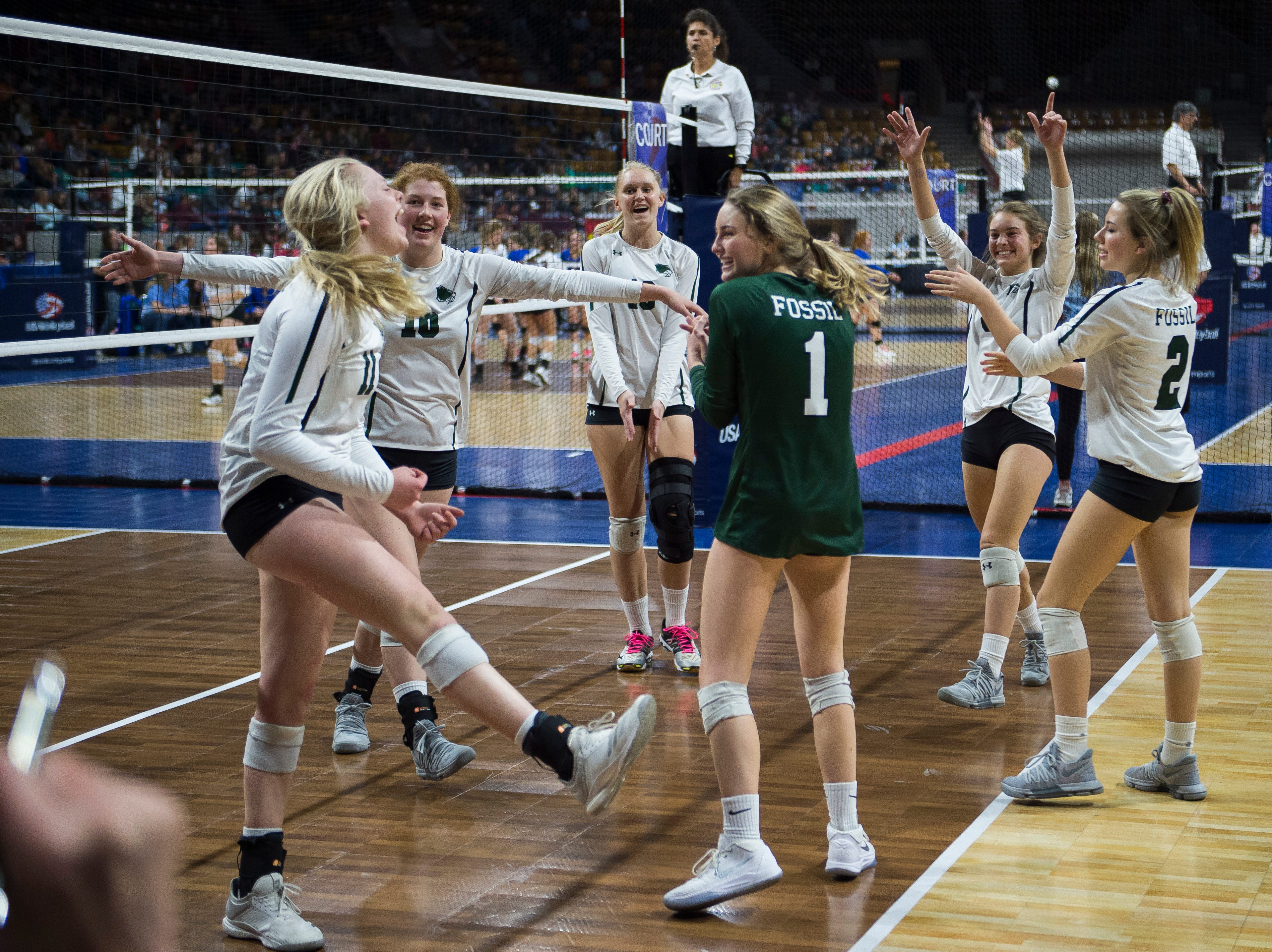 The Fossil Ridge High School volleyball team celebrate after beating Windsor High School in a state first round game on Thursday, Nov. 8, 2018, at the Denver Coliseum in Denver, Colo.