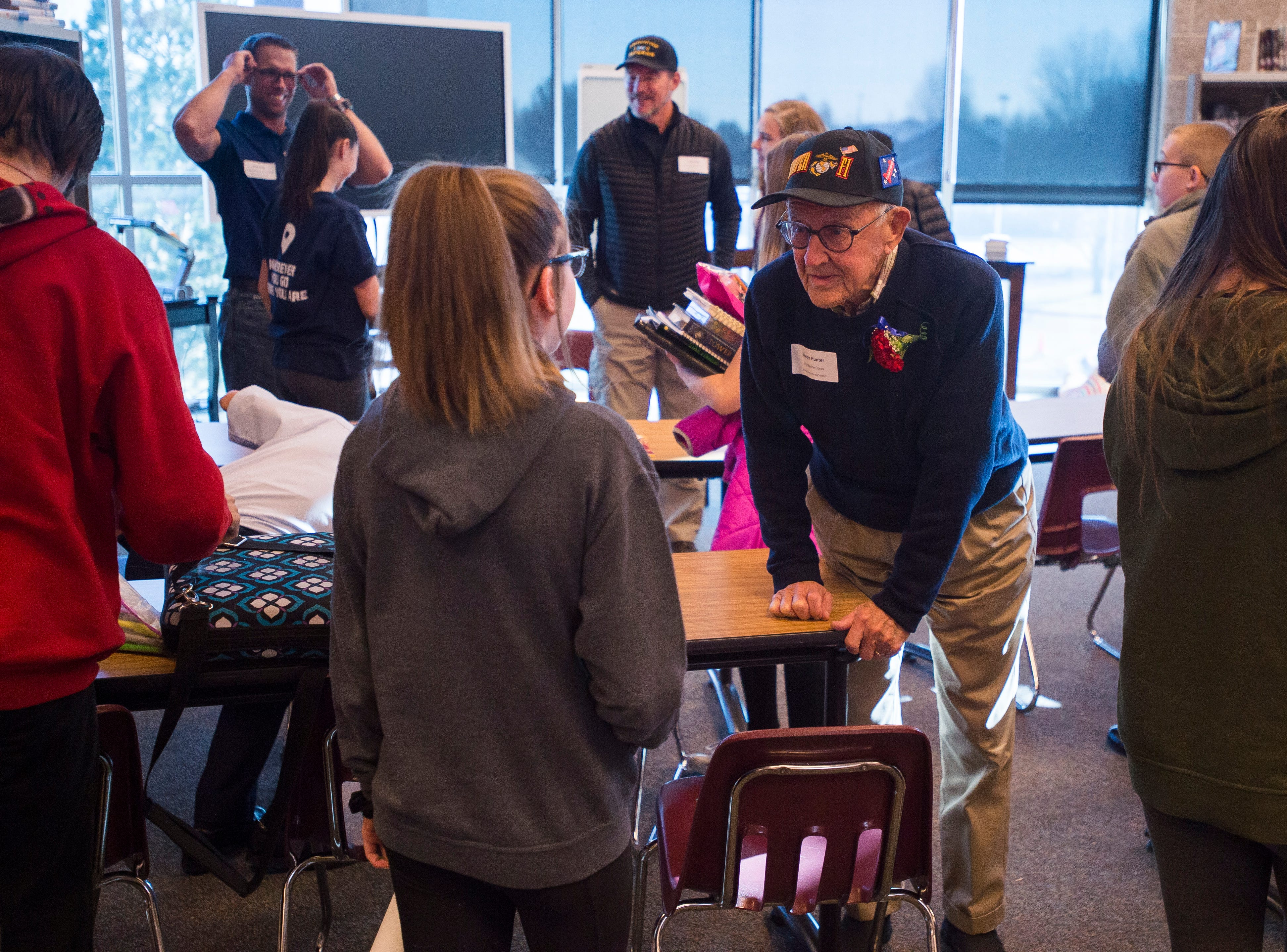 World War II Marine Corp veteran Walter Hunter chats with eighth grader Kylie Foust after speaking to a class at Preston Middle School's fourth annual Veterans Day Breakfast on Friday, Nov. 9, 2018, at Preston Middle School in Fort Collins, Colo.