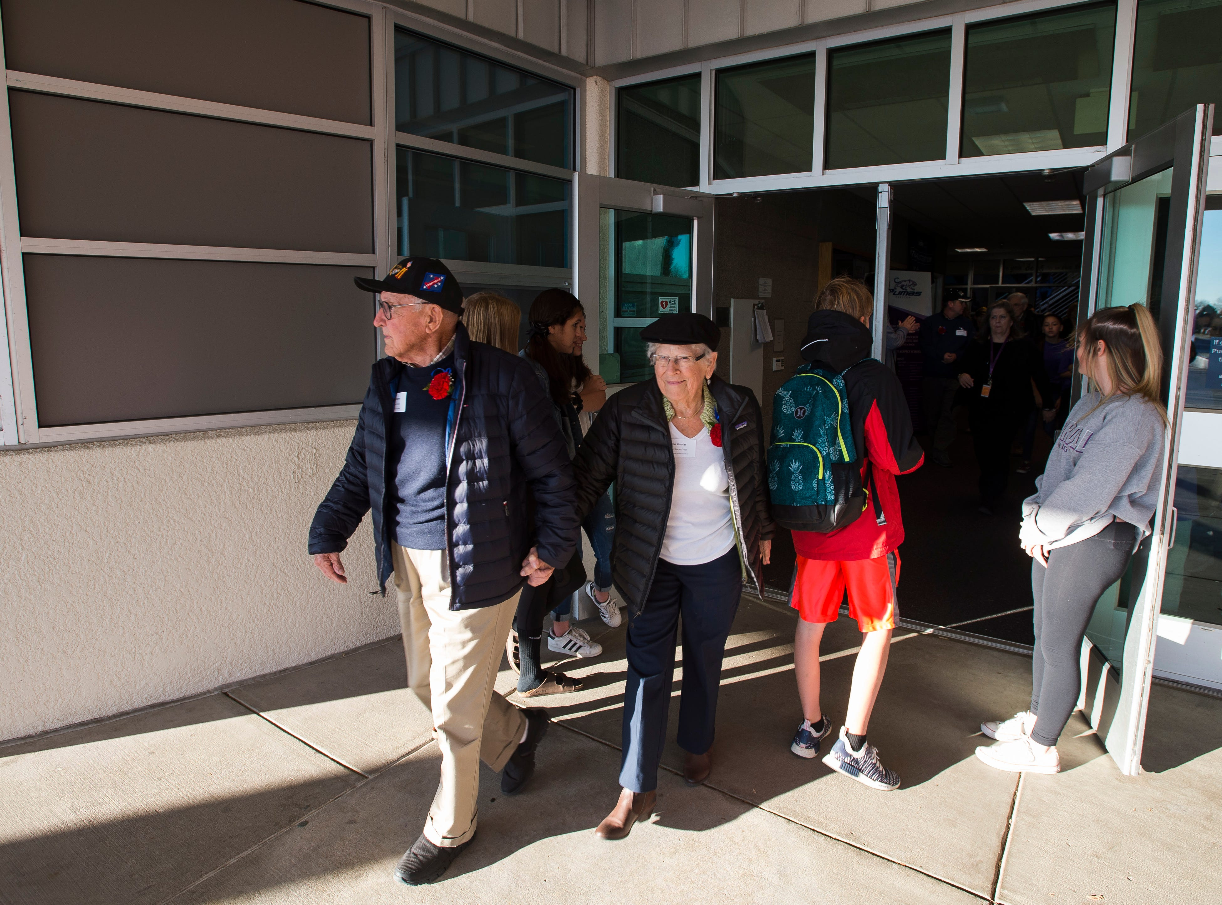World War II Marine Corp veteran Walter Hunter and wife of 72 years and World War II Cadet Nurse Corps veteran Irene Hunter head out to a special flag ceremony in front of Preston Middle School during the school's fourth annual Veterans Day Breakfast on Friday, Nov. 9, 2018, at Preston Middle School in Fort Collins, Colo.