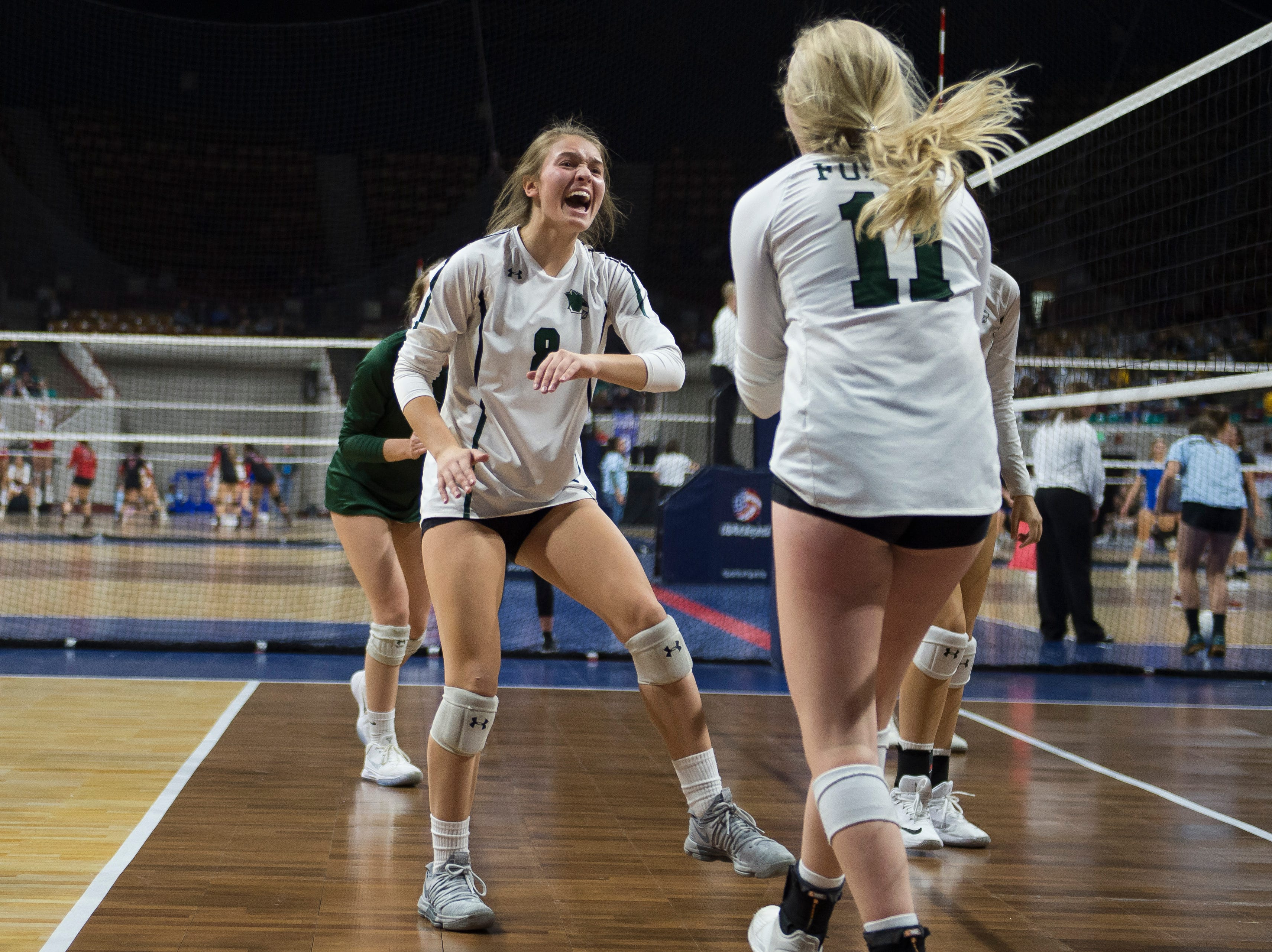 Fossil Ridge High School junior Rachel Lambrecht (8) cheers with sophomore Peyton Dunn (11) after a point against Windsor High School on Thursday, Nov. 8, 2018, at the Denver Coliseum in Denver, Colo.