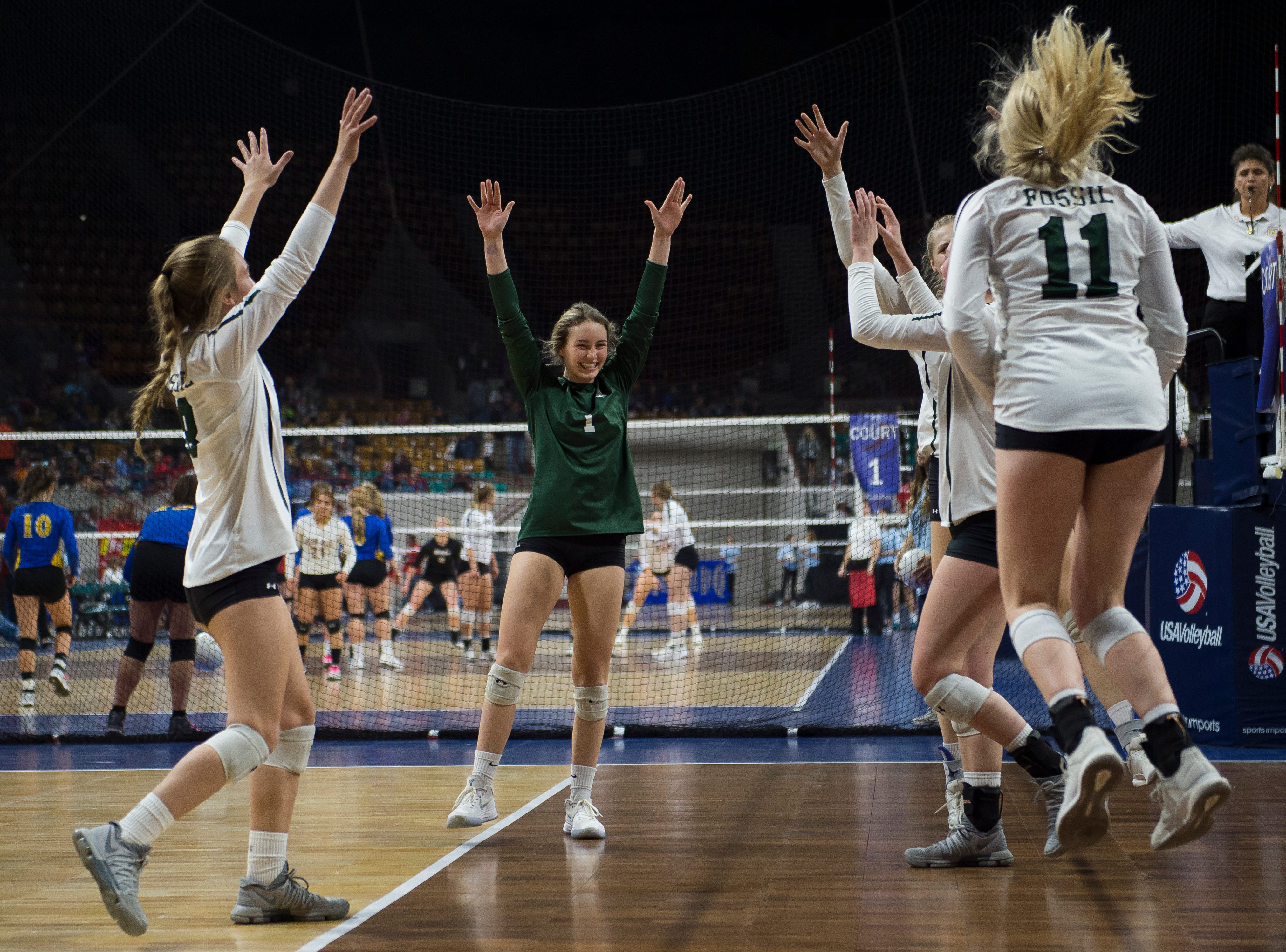 The Fossil Ridge High School volleyball team celebrate a point during a state first round game against Windsor High School on Thursday, Nov. 8, 2018, at the Denver Coliseum in Denver, Colo.