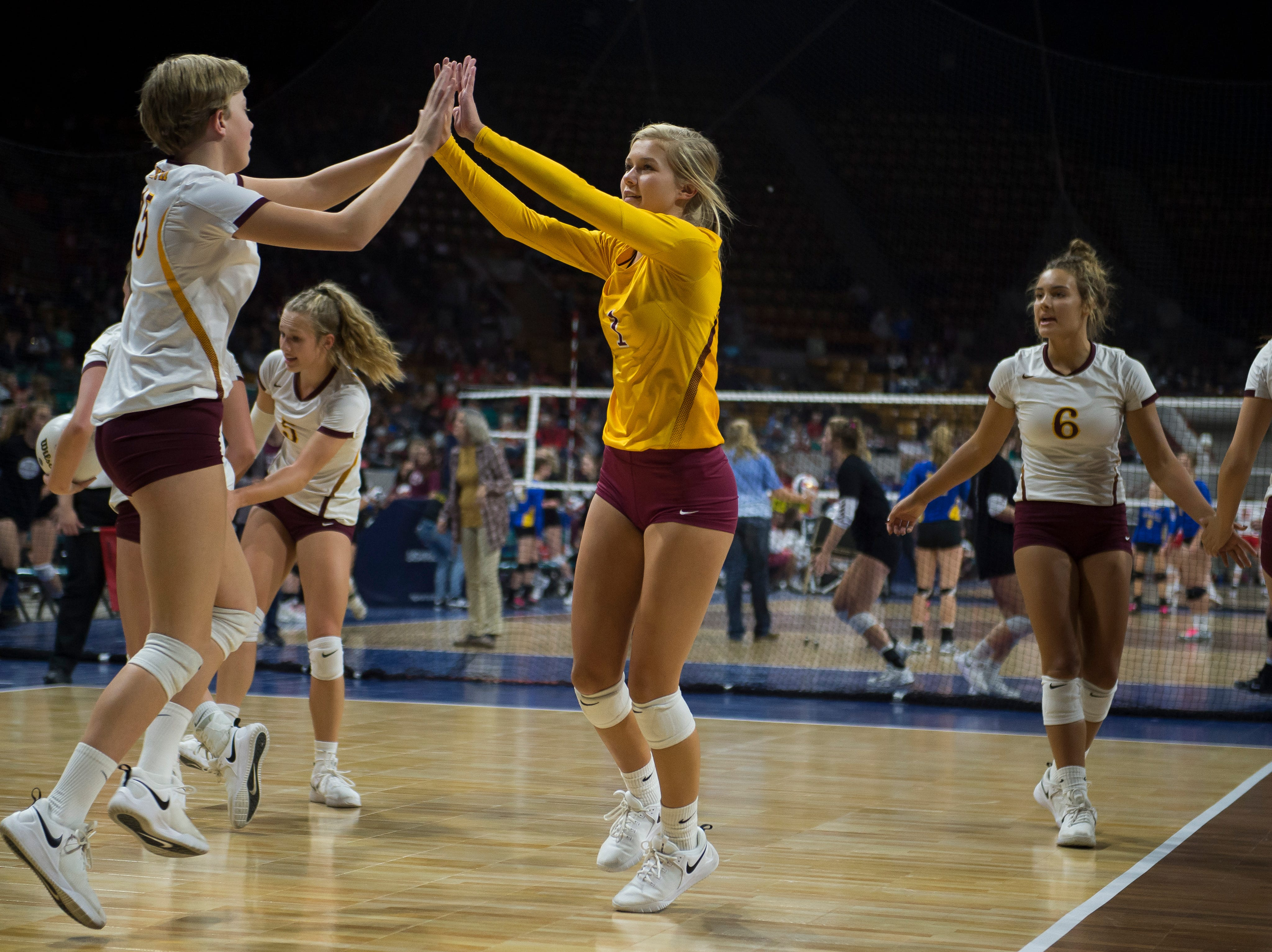 Windsor High School senior Hollie Hoffman (1) high fives teammate Adison Moyer (15) during a state first round game against Fossil Ridge High School on Thursday, Nov. 8, 2018, at the Denver Coliseum in Denver, Colo.