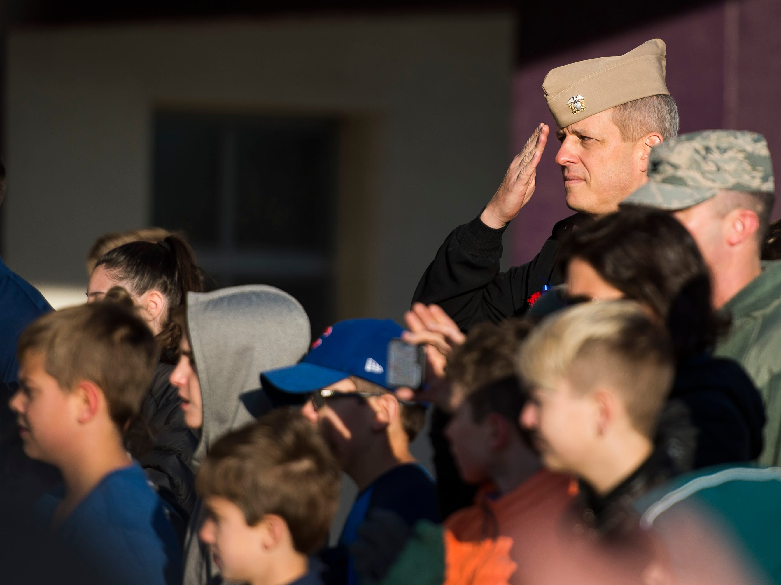"United States Navy veteran John Roberts salutes the flag while Preston Middle School students sing ""The Star-Spangled Banner"" on Friday, Nov. 9, 2018, at Preston Middle School in Fort Collins, Colo."