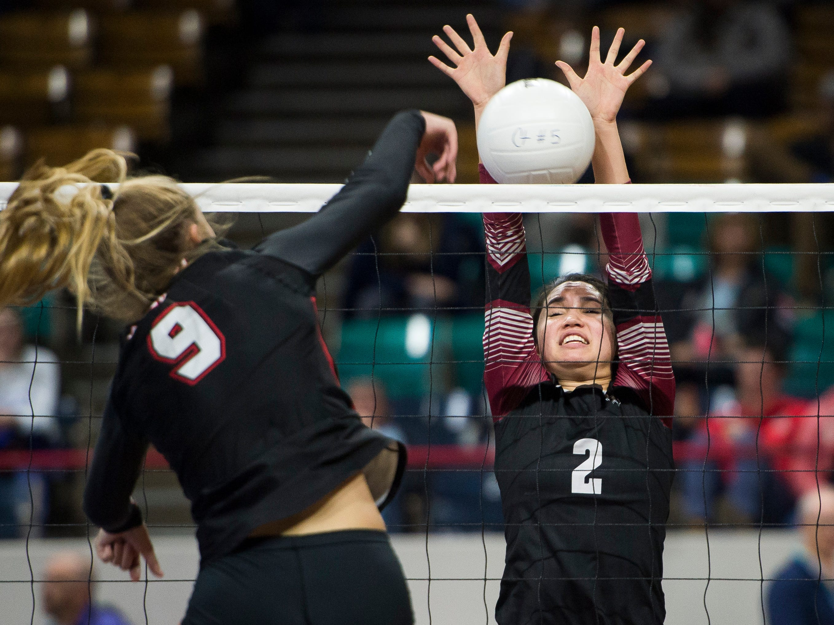 Rocky Mountain High School junior Kiki Mayes (2) blocks a spike by Eaglecrest junior Gabreille Vogt (9) during a first round state game on Thursday, Nov. 8, 2018, at the Denver Coliseum in Denver, Colo.