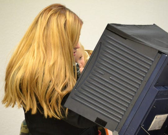 Scarlett Smith, 1-1/2, lays quietly as her mother Lakyn Smith votes in the Nov. 6 election at Oconto City Hall.