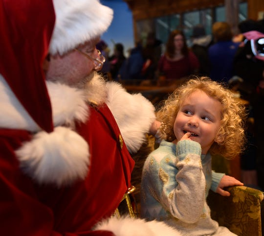 Santa listens to the Christmas wishes of Abigail Smullen of Sturgeon Bay, as he did for many other children, following last year's Holiday Parade in Sturgeon Bay.