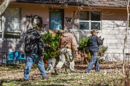 Law enforcement and a K9 walk on the property Tuesday, Oct. 16, 2018, during an investigation of a couple found dead in their house in Barron, Wis.