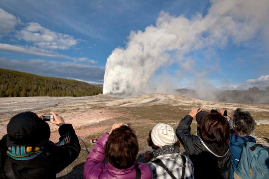 FILE - In this May 21, 2011, file photo, tourists photograph Old Faithful erupting on schedule late in the afternoon in Yellowstone National Park, Wyo. A 27-year-old Colorado man who walked dangerously close to Old Faithful geyser in September 2018, is banned from Yellowstone and Grand Teton national parks for five years. (AP Photo/Julie Jacobson, File)